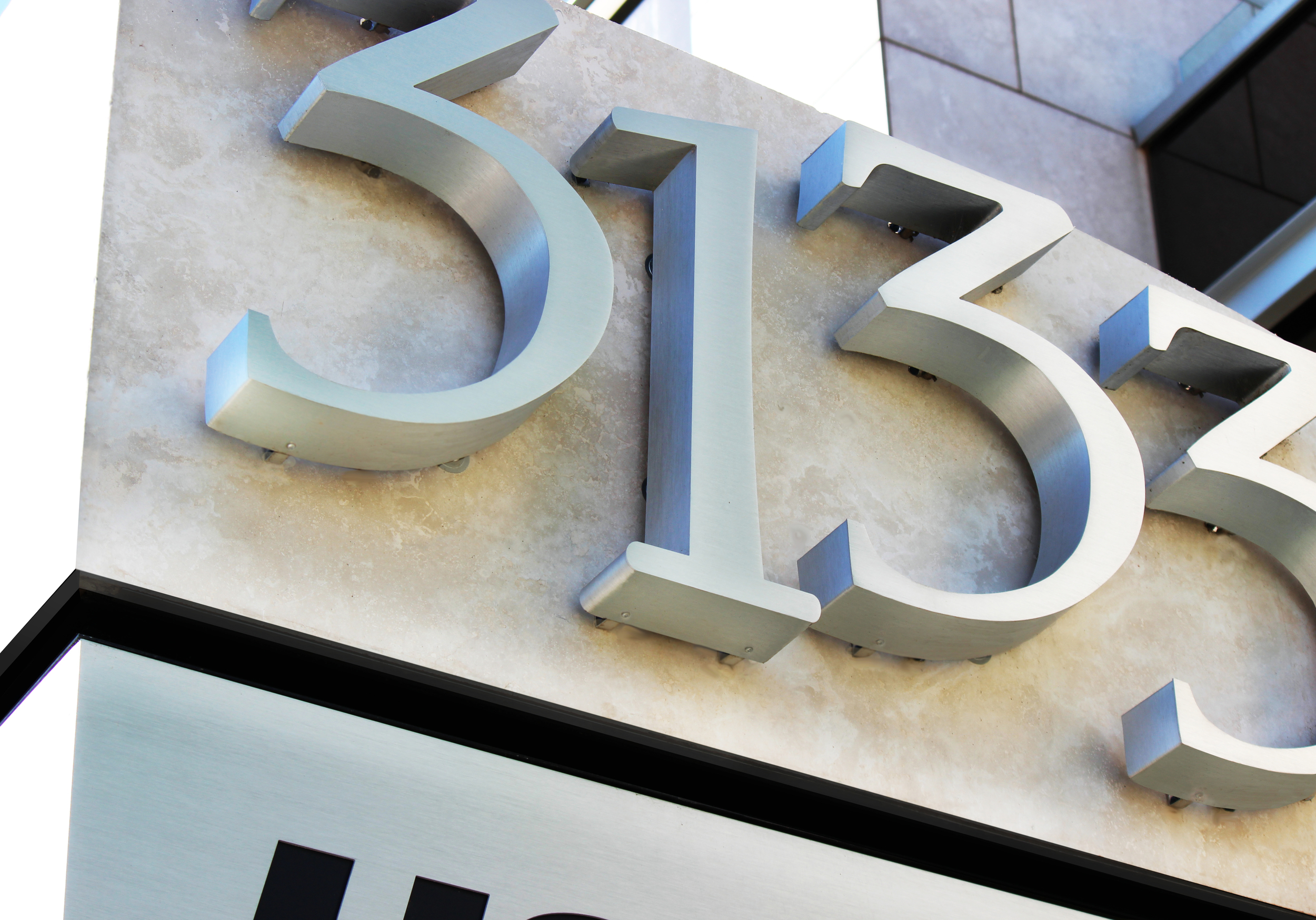 The halo-lit address is fabricated using stainless steel and LEDs. The numbers are mounted to travertine slab.