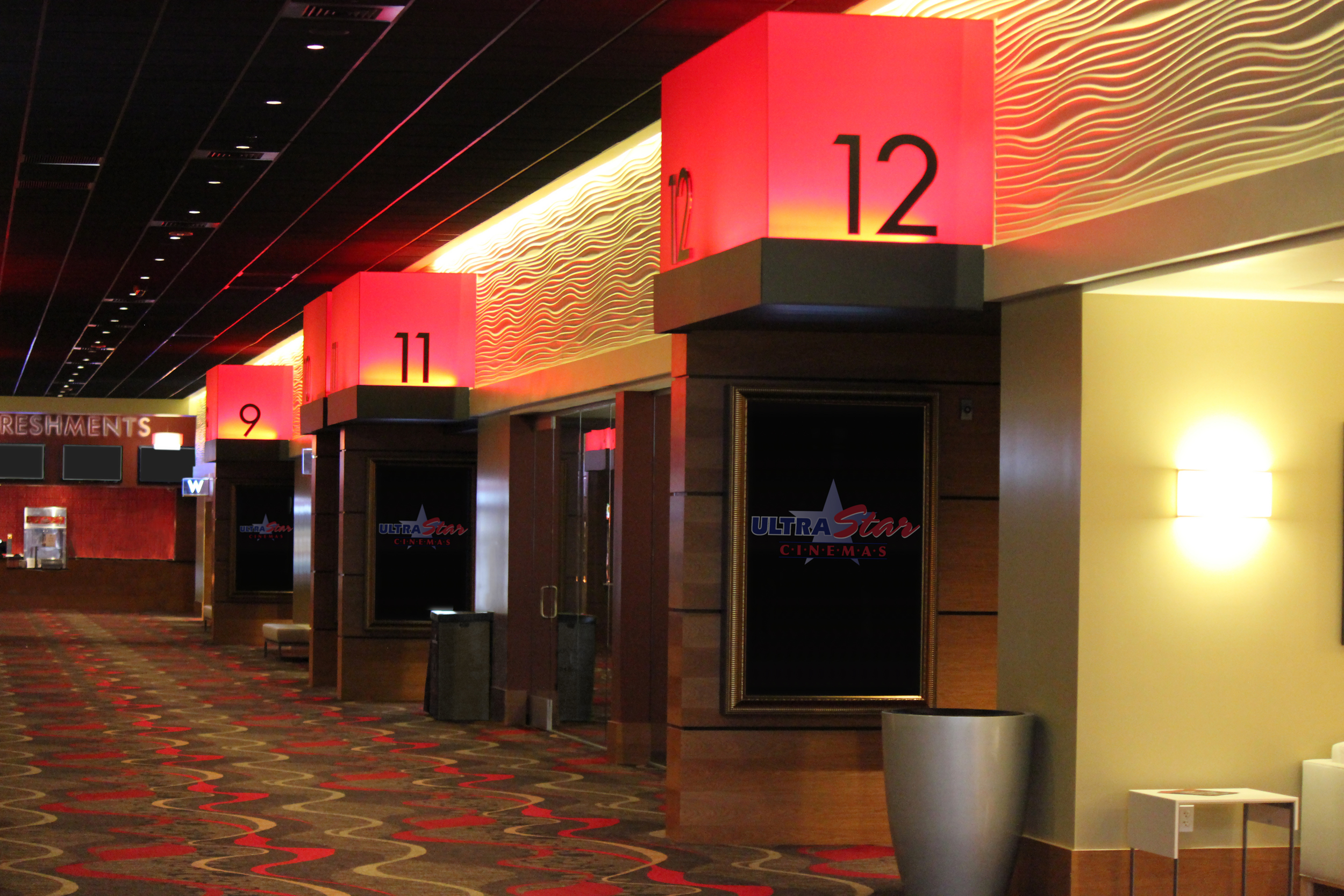 Custom acrylic boxes and flat cutout lettering marks the entrances to each theater.