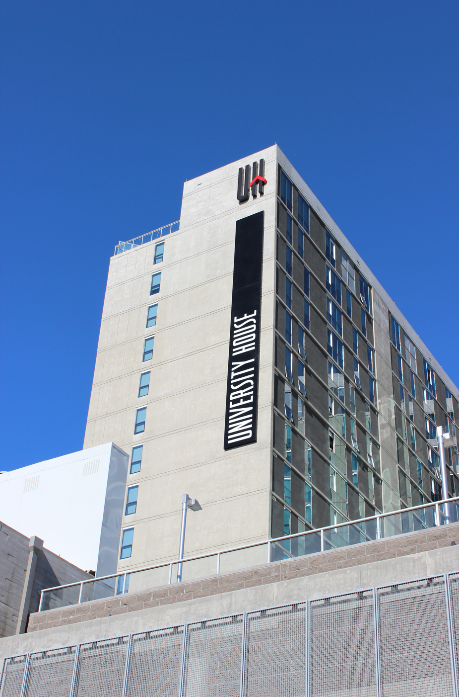 University House's logo is illuminated as a building top sign. The over 80' long sign can be seen from across the ASU campus in Downtown Tempe.