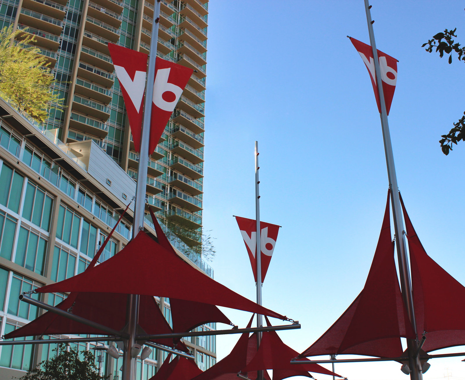 Residents enjoy the courtyard's park like flagpole installation. The flagpoles create shade with custom sails and have lighting and W6 elements to attract branding attention from Mill Avenue.