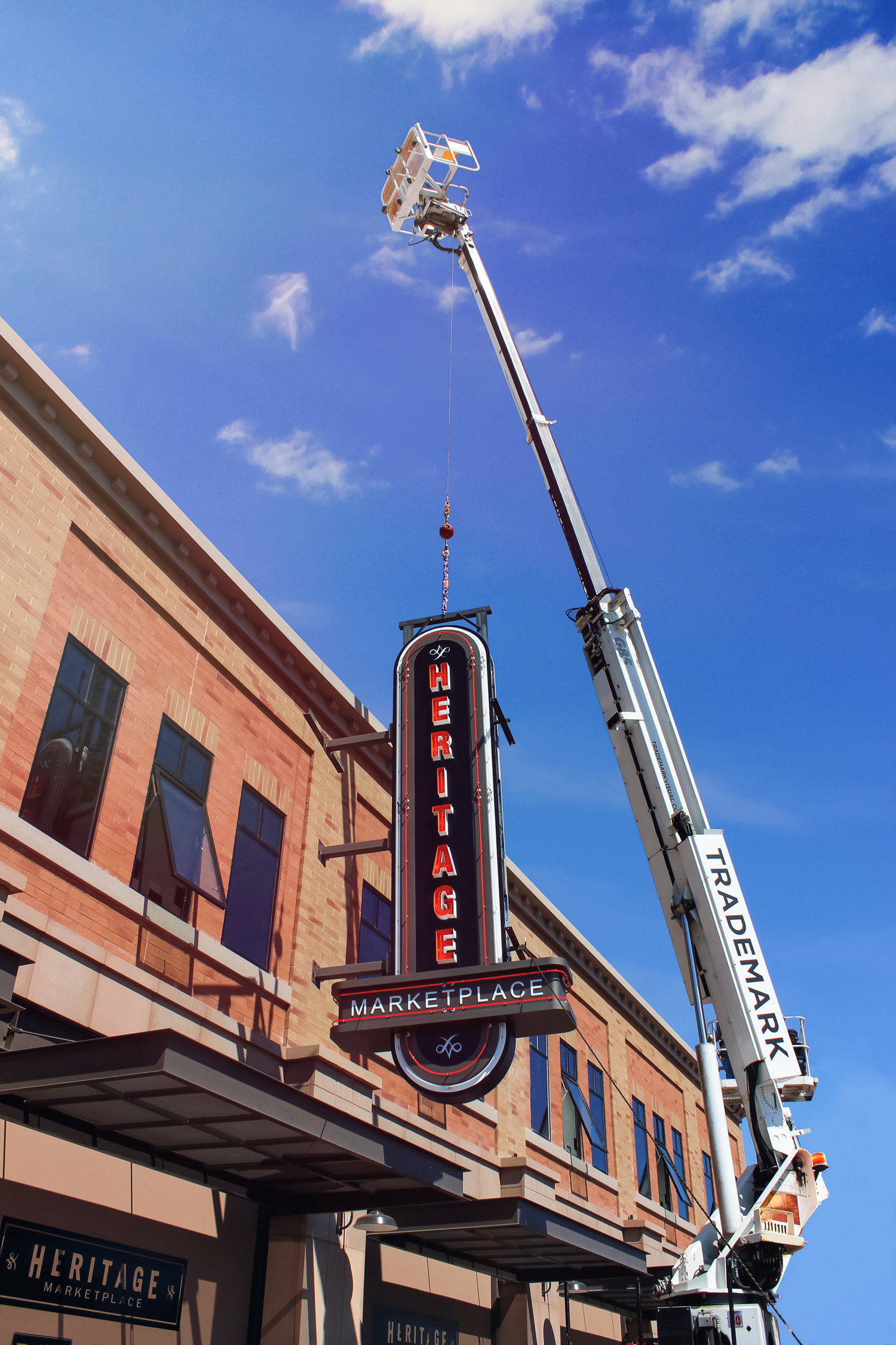Trademark's crane is proudly installing the illuminated blade sign.