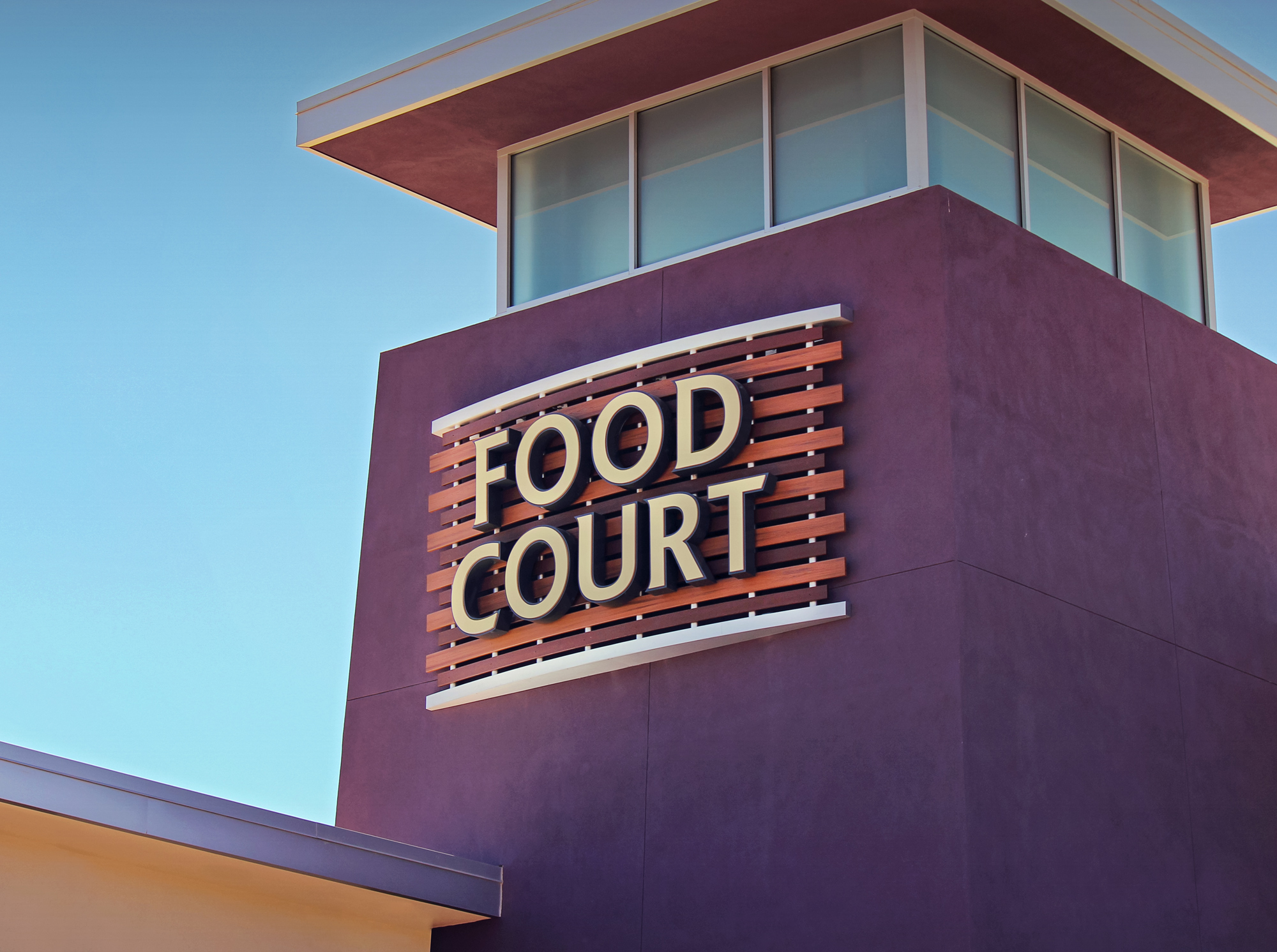 The illuminated tower top sign with wood accents promote the multi-restaurant food court.