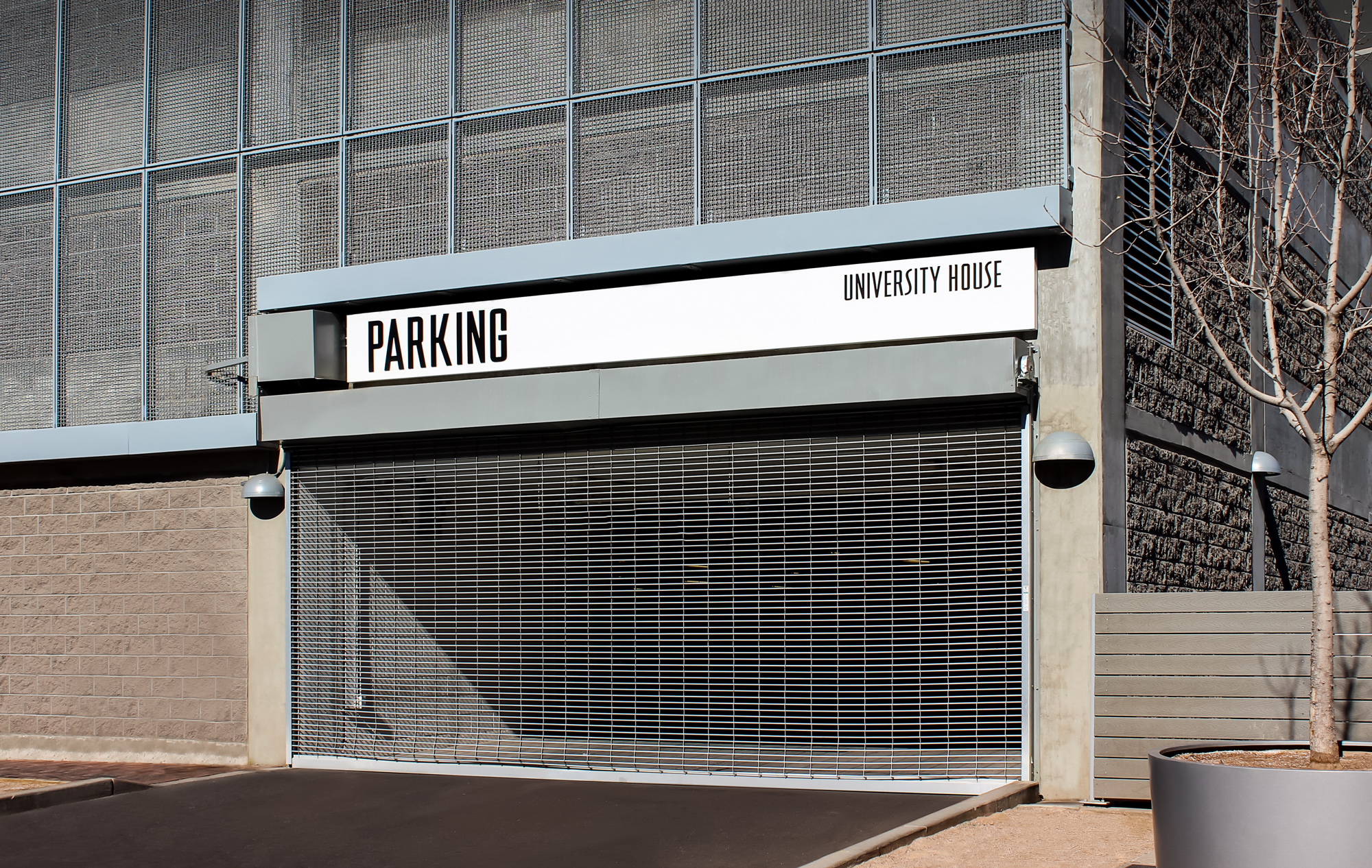 A simple black and white sign signals traffic to the parking garage entrance.