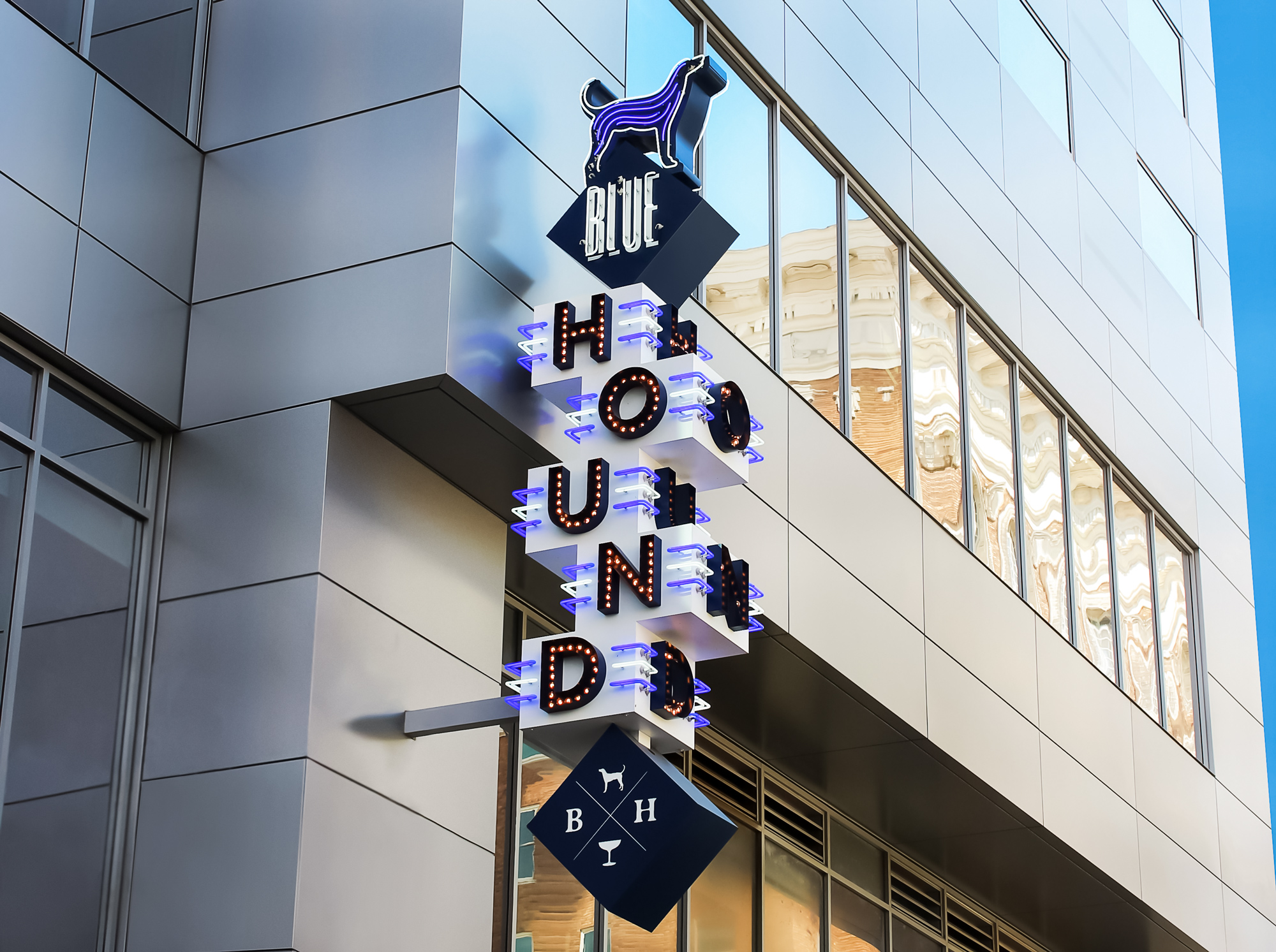 A 30' tall three sided blade sign with exposed neon and filament bulbs.