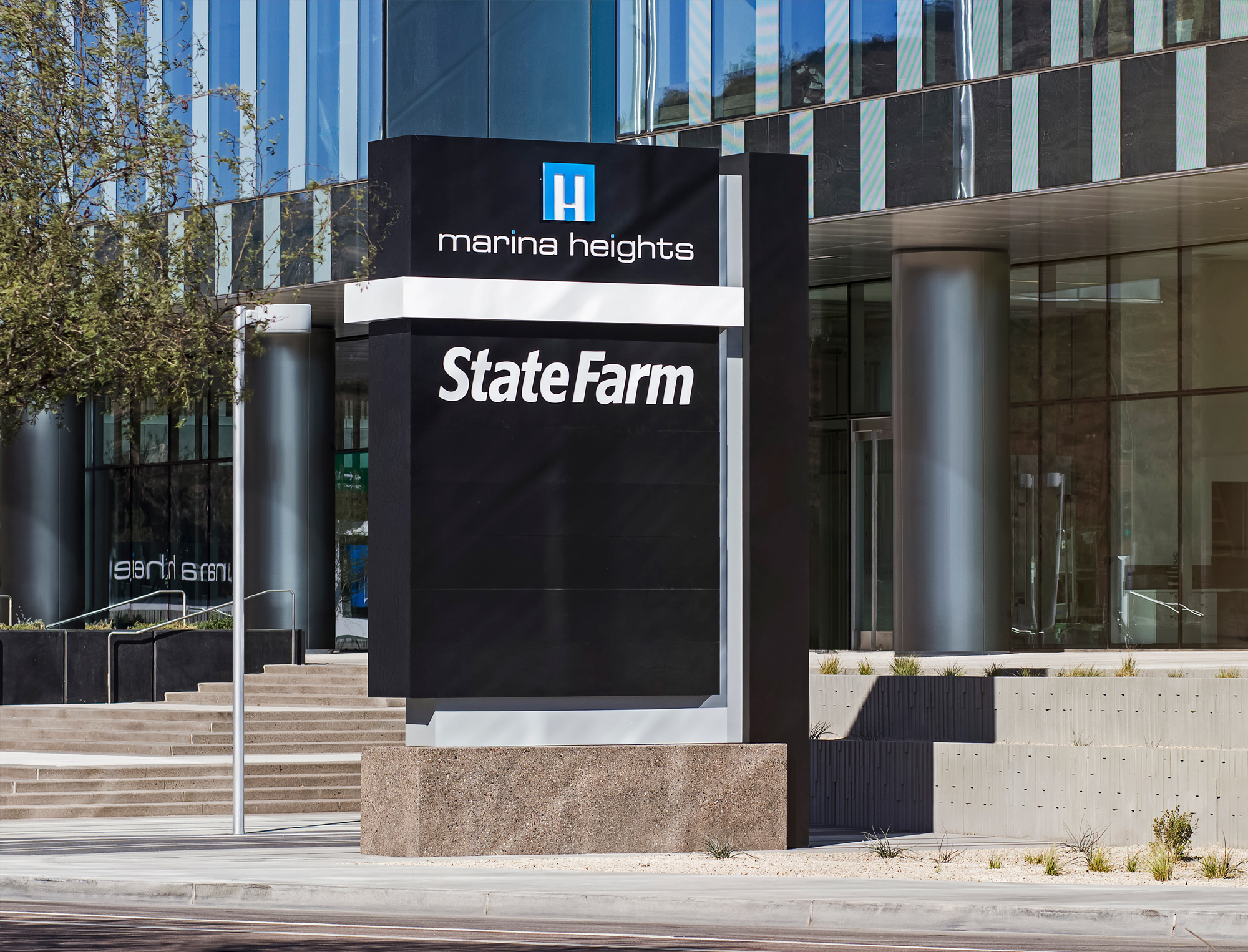 An opposite angle of the LED illuminated multi-tenant ground sign.The State Farm Insurance tenant panel is prominent and extremely legible given the use of contrasting color.