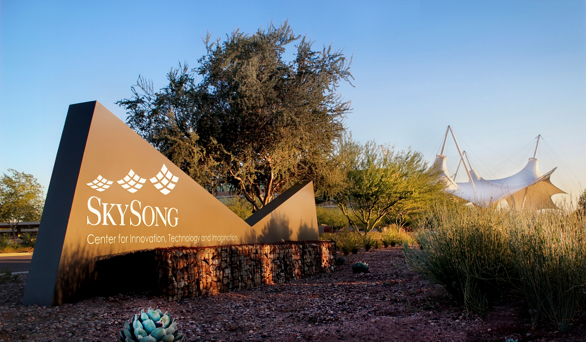 A double blade, triangular shaped ground sign with Gabion basket planter beds.
