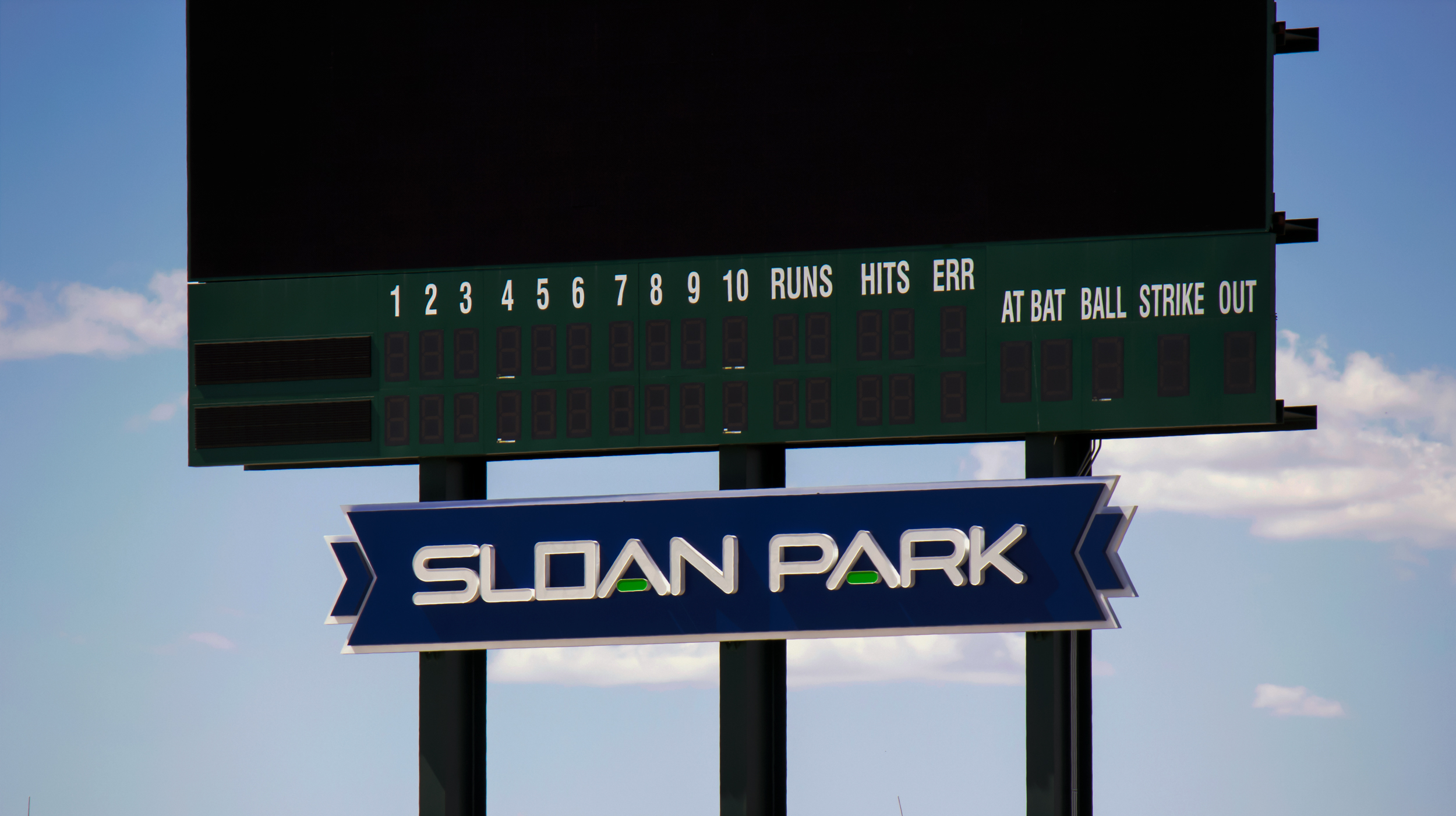 The double faced illuminated cabinet sign brands the spring training field scoreboard Sloan Park.