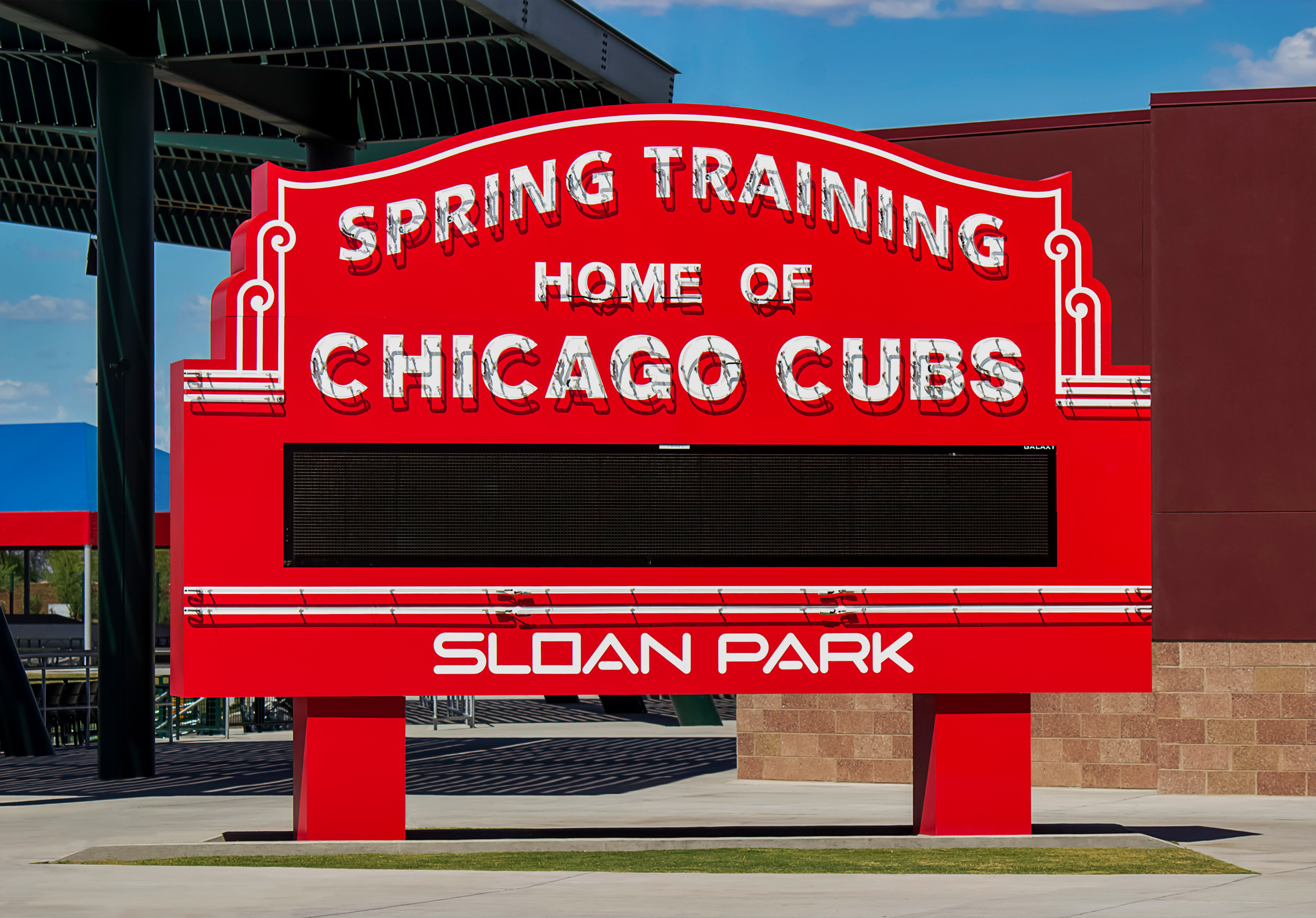 A freestanding replica of the iconic Wrigley Field sign is installed at Sloan Park. The sign is complete with exposed skeleton neon and an electronic message center.