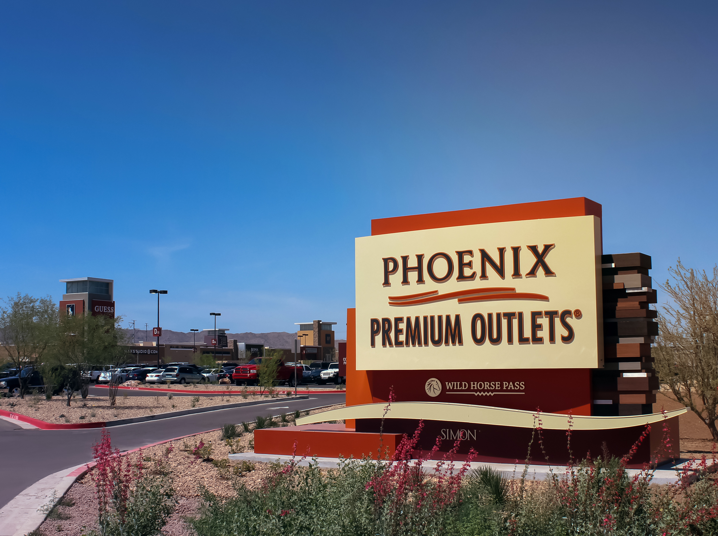 A single sided illuminated monument directs shoppers to the outlet's entrance. The acrylic push through lettering creates glow around the aluminum panel.