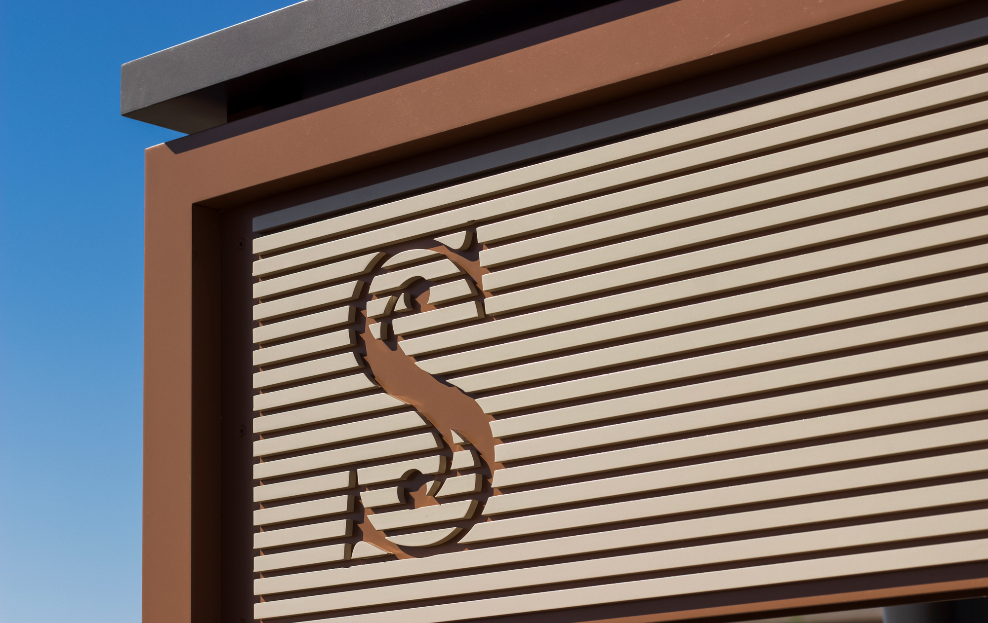 An up close photo of detailed logo.  The logo is created from routed aluminum panels to create the embellished S.