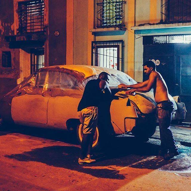 Friends work on restoring a classic car under the amber streetlights of Havana's seaside district. Cuba is officially my new back yard. Looking forward to capturing more of this amazing country. #fujix100f