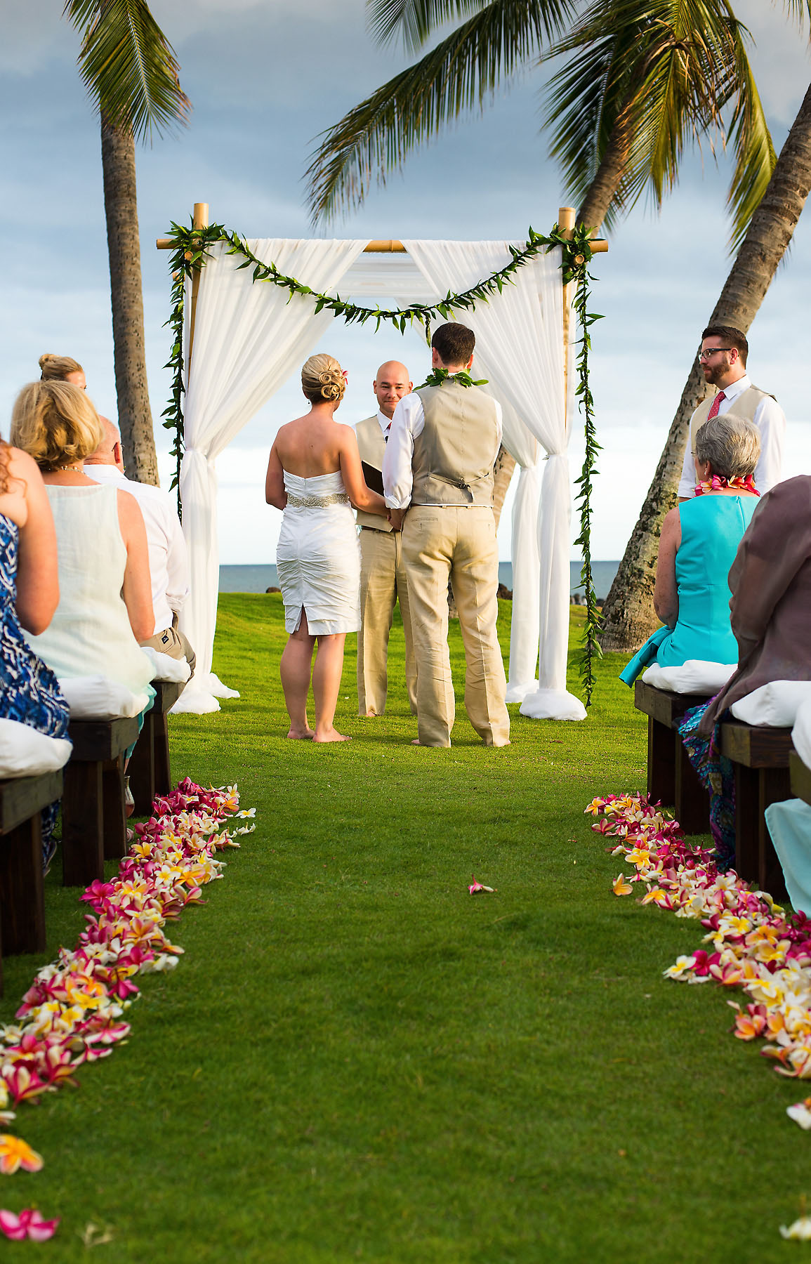 A Beach Wedding Ceremony with Flowers Along the Aisle and Palm Trees in the Background in Maui, Hawaii. Photo Credit: Jared Lawson Photography
