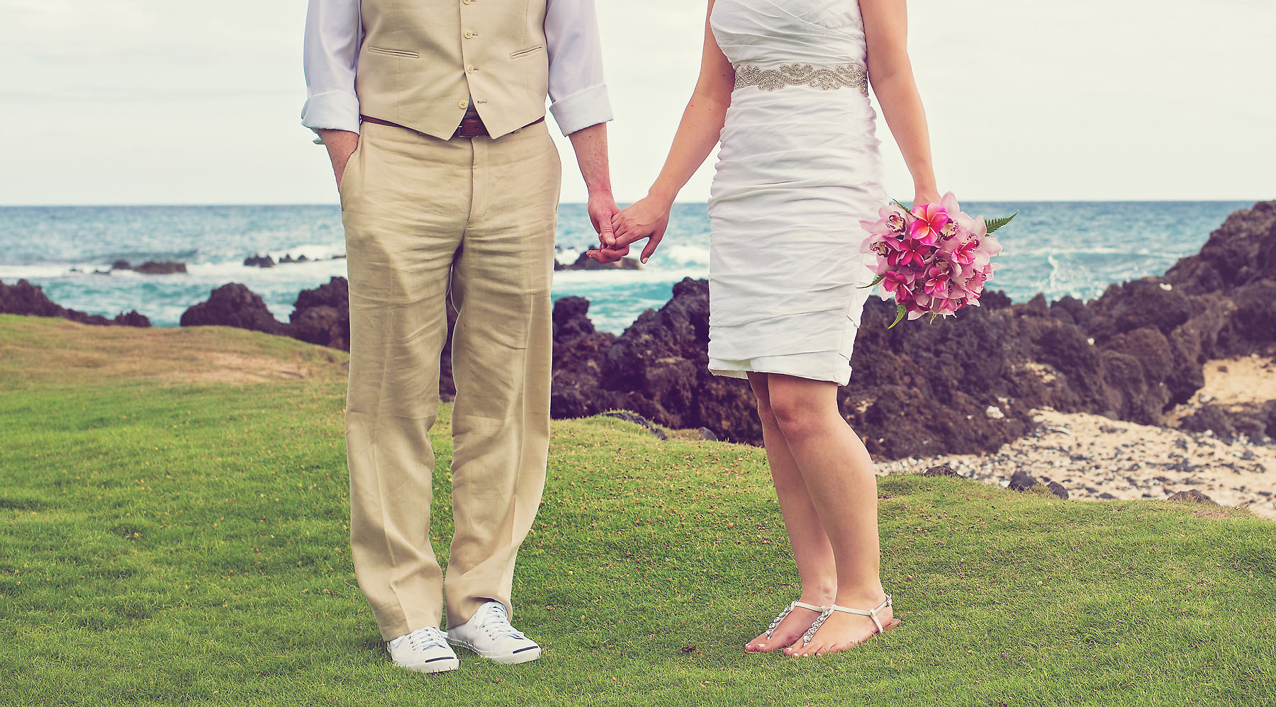 Bride and Groom Hold Hands in this Beach Wedding in Maui, Hawaii with the Ocean and Rocks in the Background. Photo Credit: Jared Lawson Photography