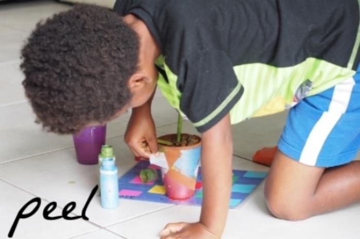 child paints flower pot