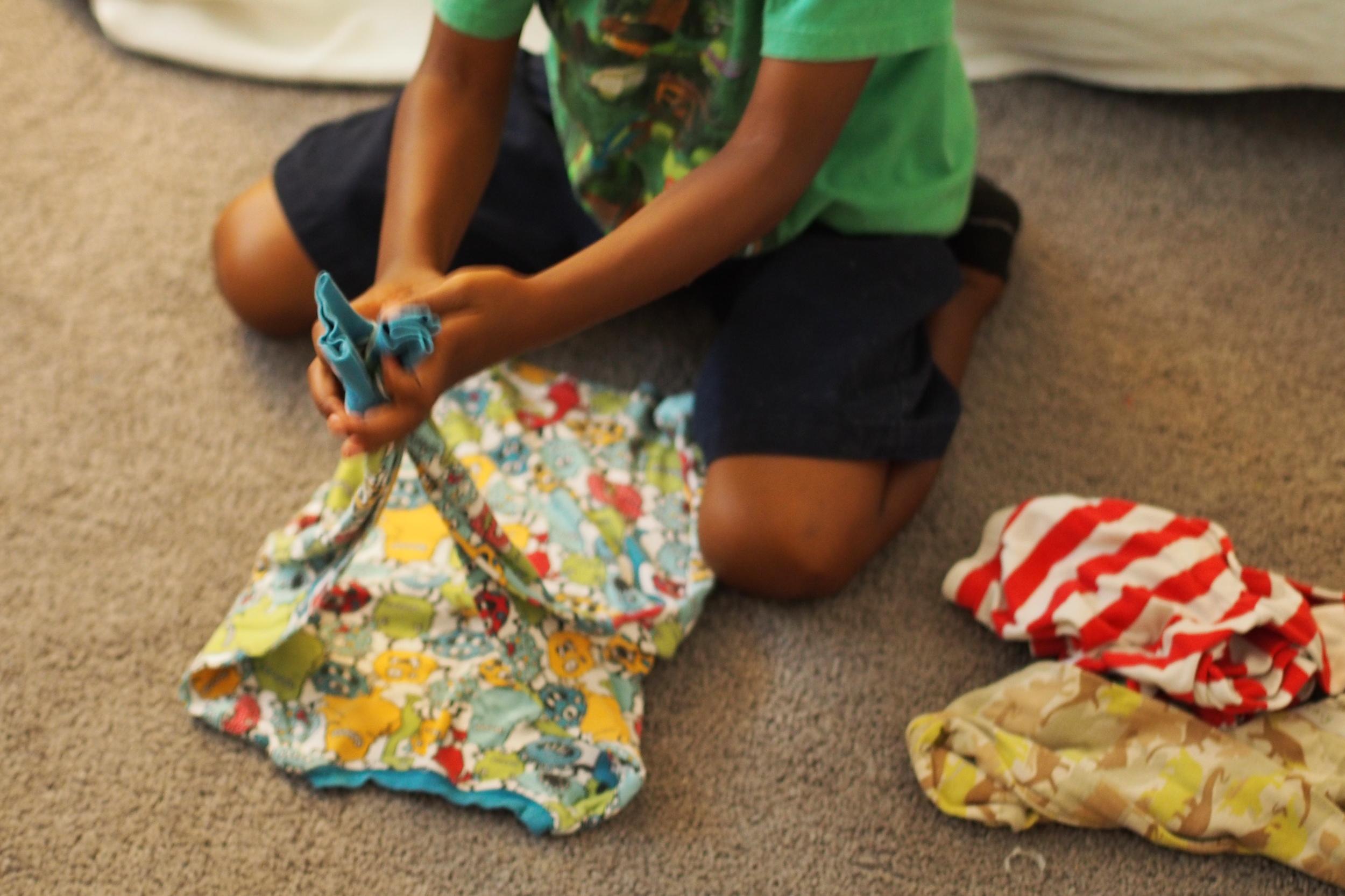 child folds clothing