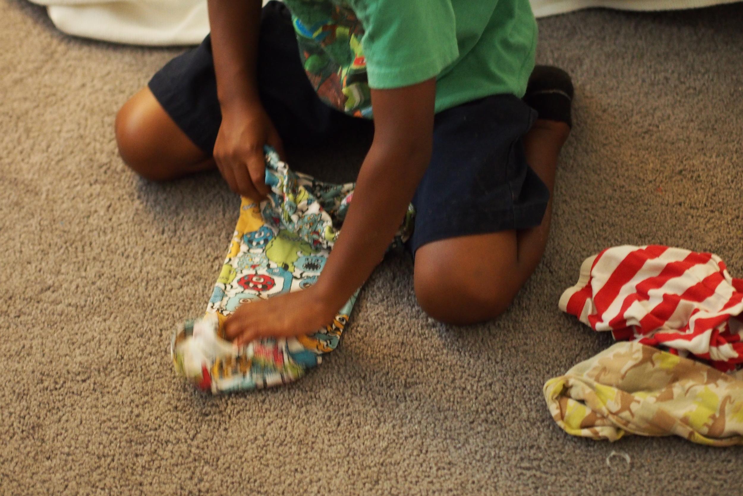 child folding clothing