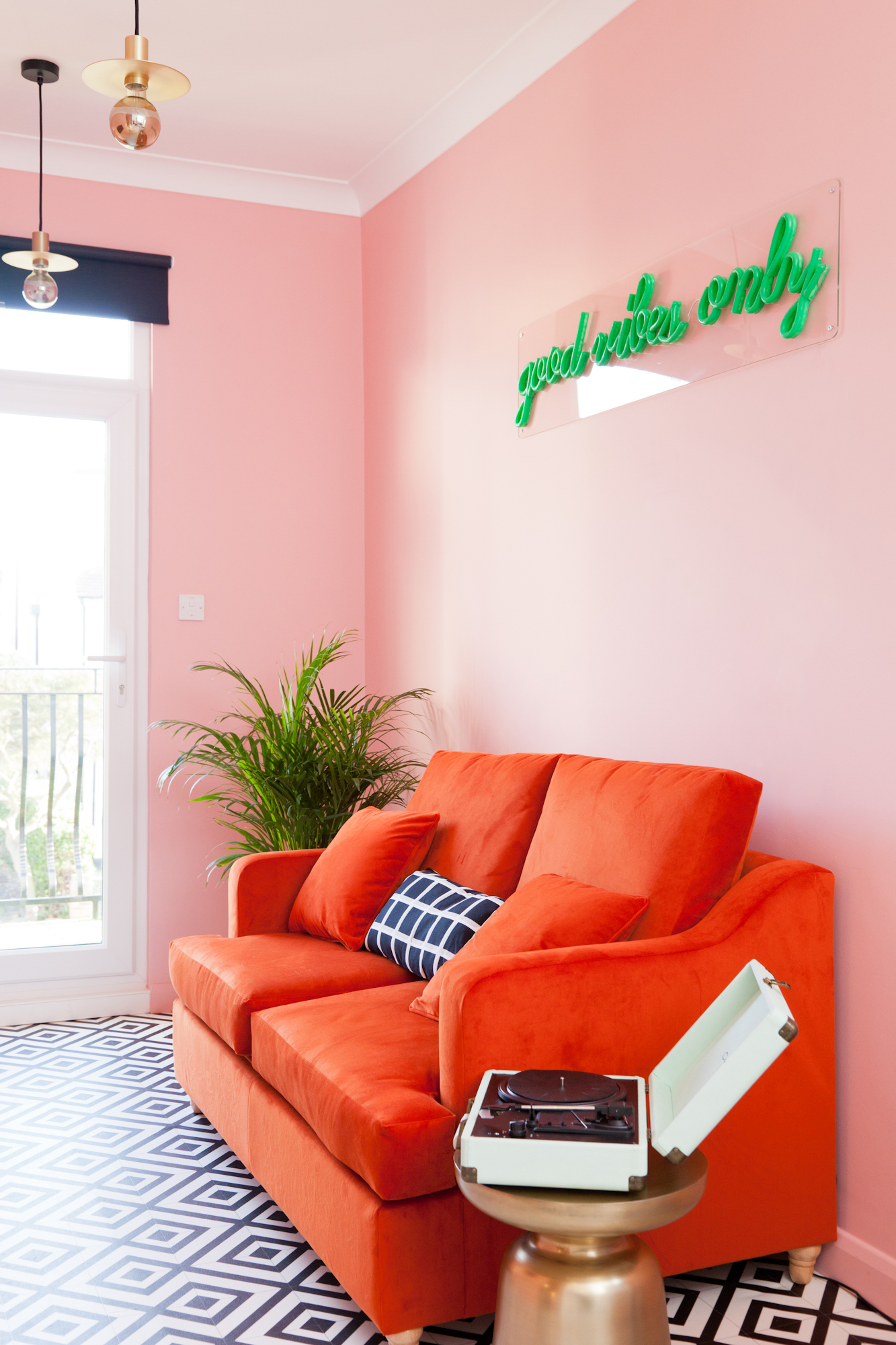 Here are the reveal pictures of my latest interior design project, an eclectic decor with pink walls, brass accents a red velvet sofa, neon signs and dark walls in the bedroom.