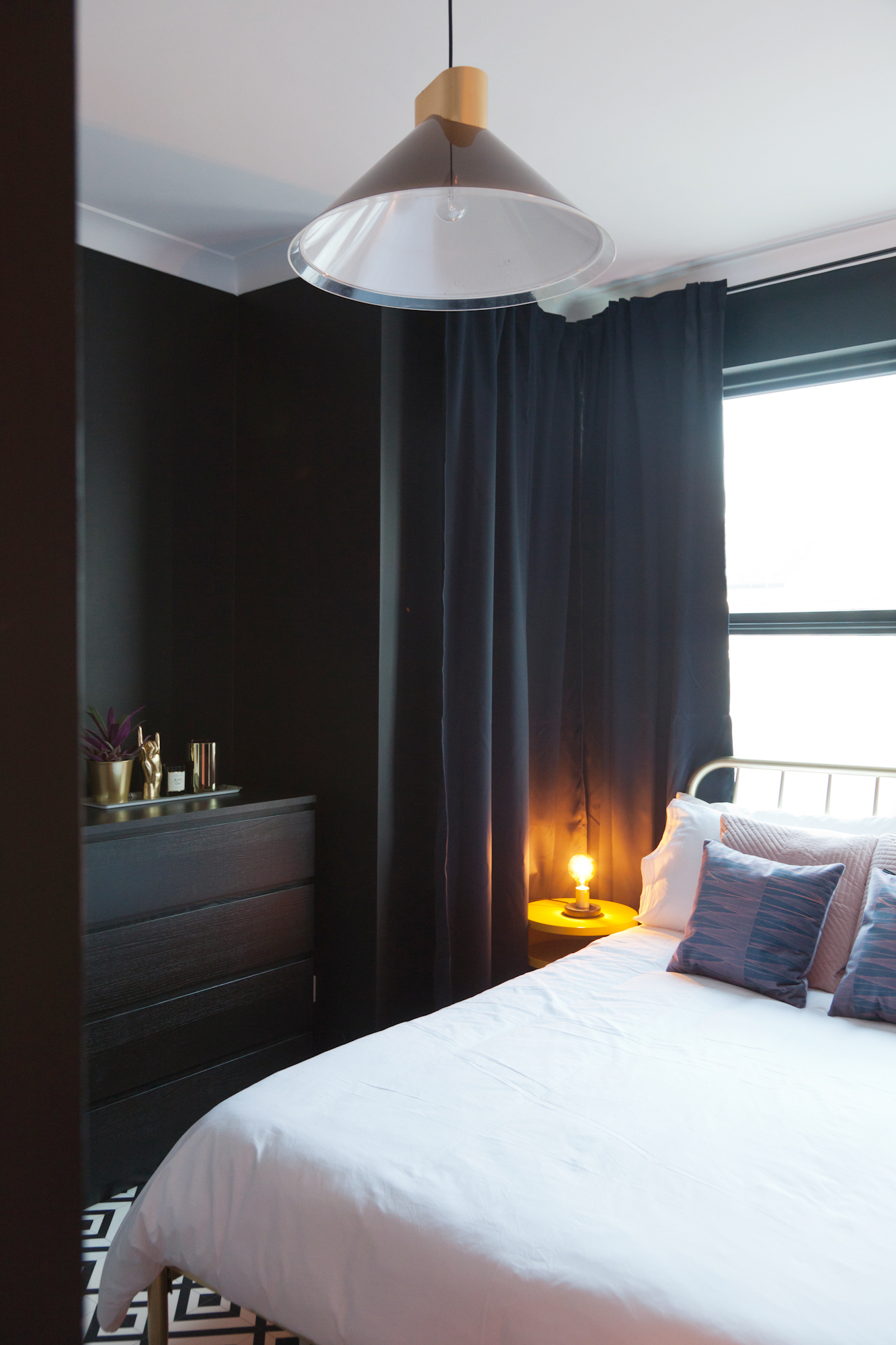 In the bedroom I created an eclectic decor look with black matte walls, gold accents, black and white geometric flooring and a custom neon sign.