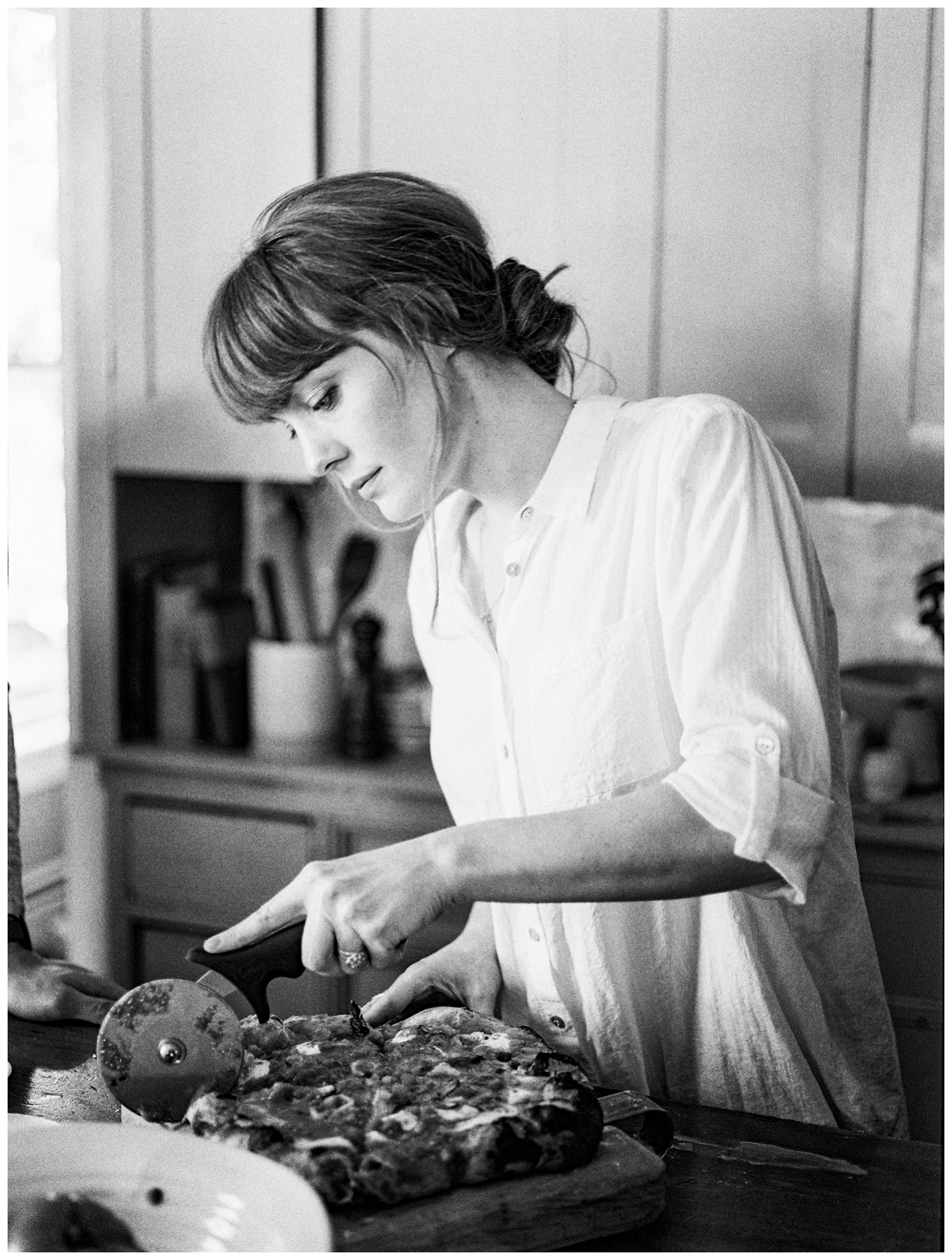 culinary anniversary session in the kitchen with a couple cooking pizza together by fine art photographer Lissa Ryan Photography