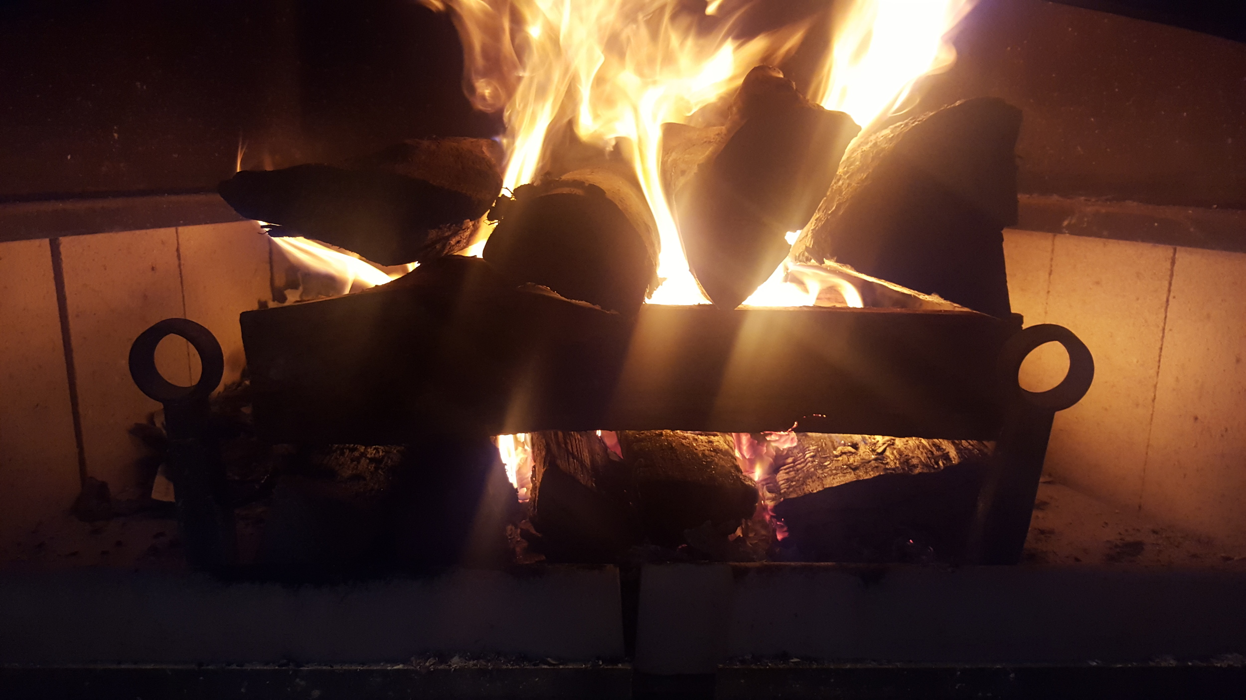 Firewood added in similar cob formation on top of embers from kindle fire