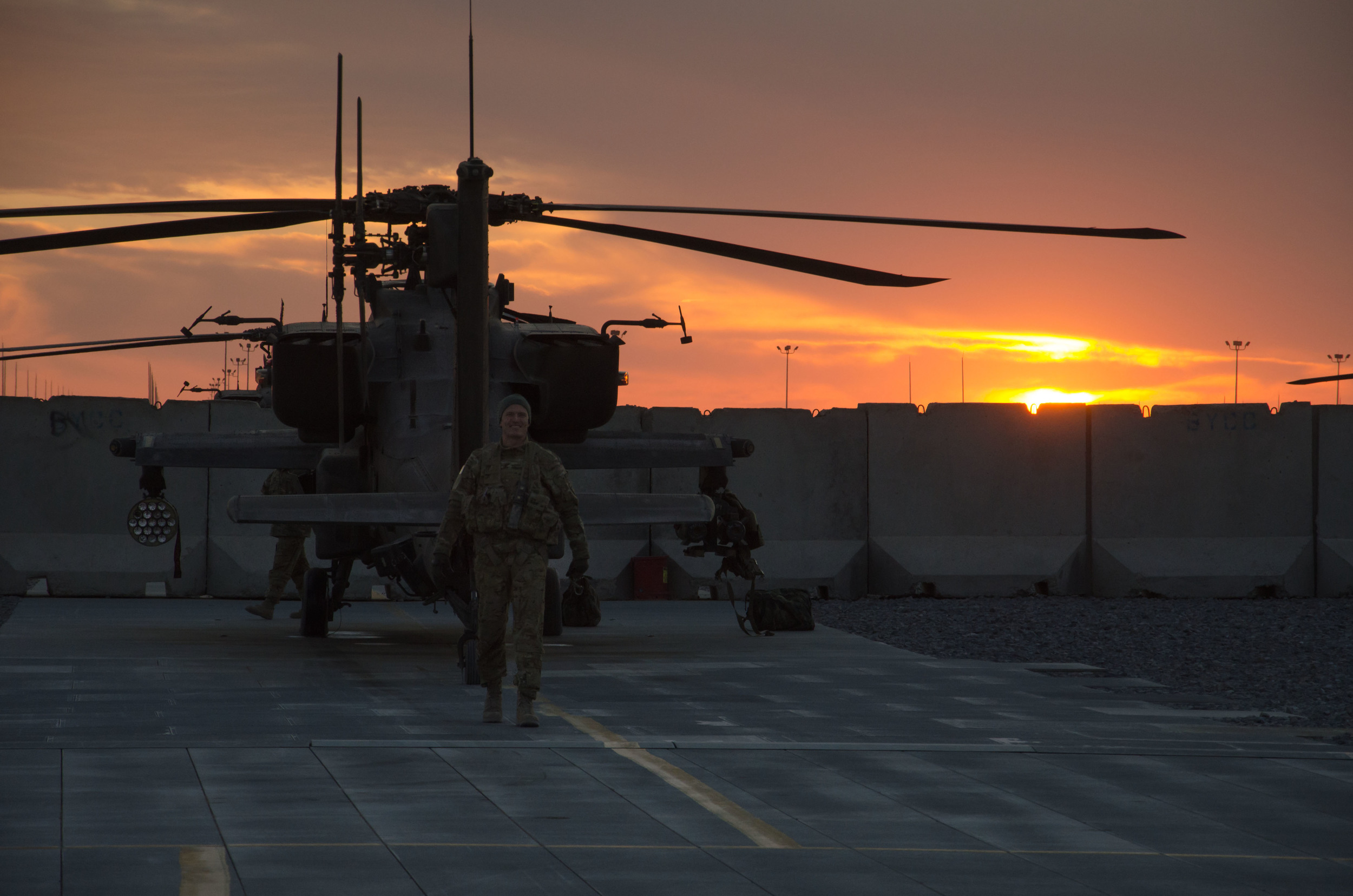 Apache pilot smiles for the camera as he finishes his shift, and ends his day with a beautiful evening sunset shot.