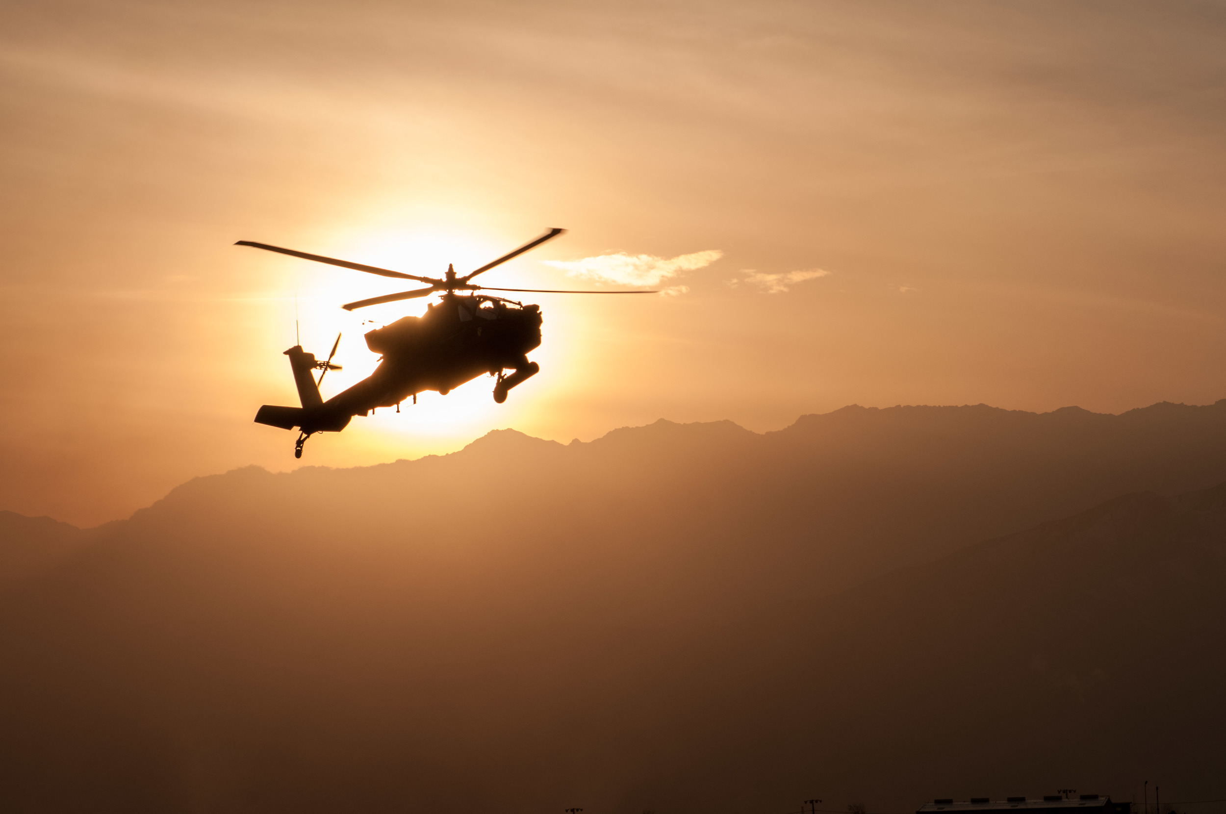 Beautiful capture of an Apache helicopter right as the sun was attempting to hide behind the mountains.