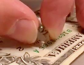 Lente mecanizada en la máquina Pocket NC V2-10 con letras de aumento en un dólar estadounidense.