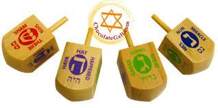 dreidels showing Hebrew letters Shin, Heh, Gimel, and Nun respectively