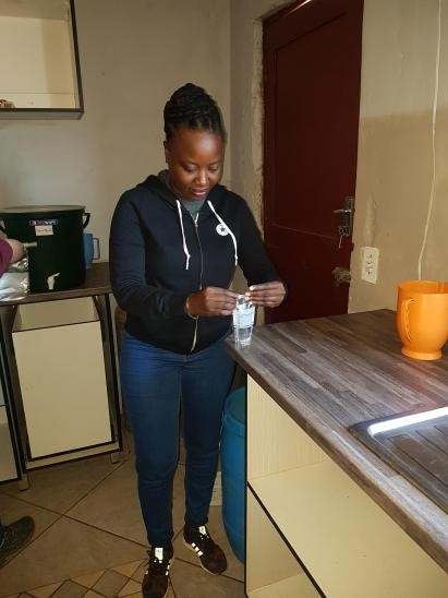 Nkosi during water sample collection at one of the participating households in Dertig