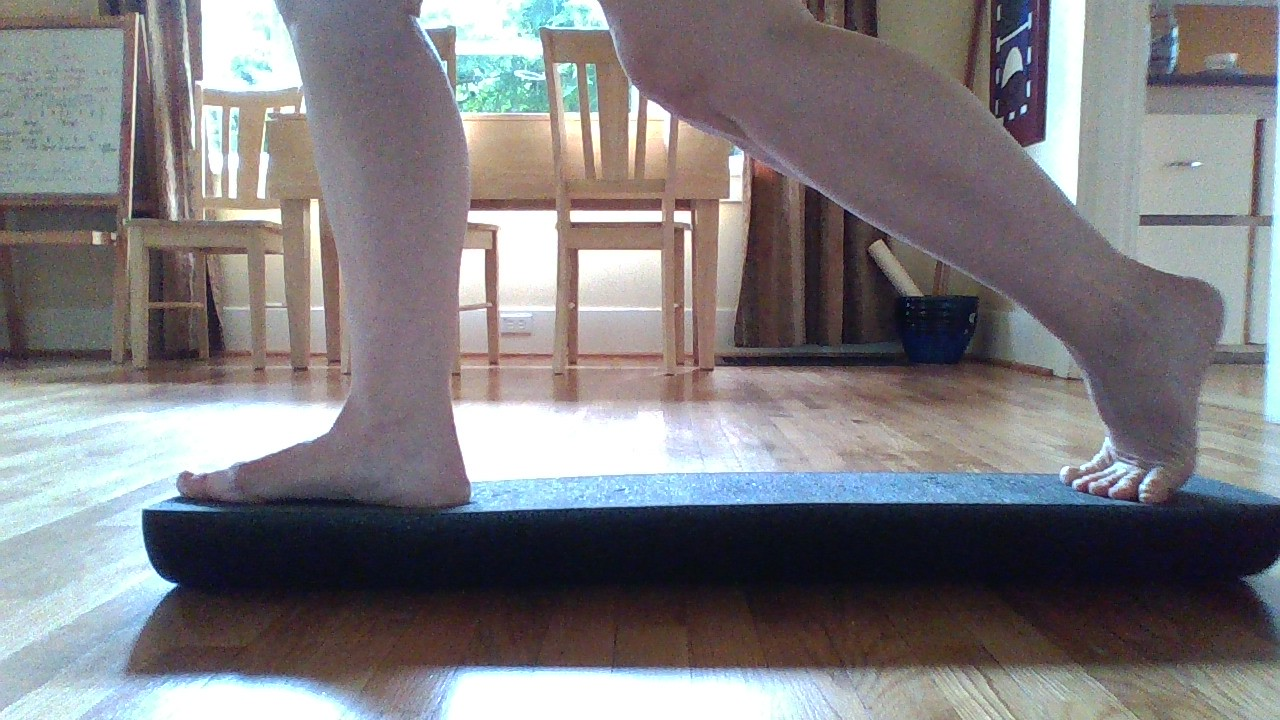 BOTH feet on the roller, hard side up.