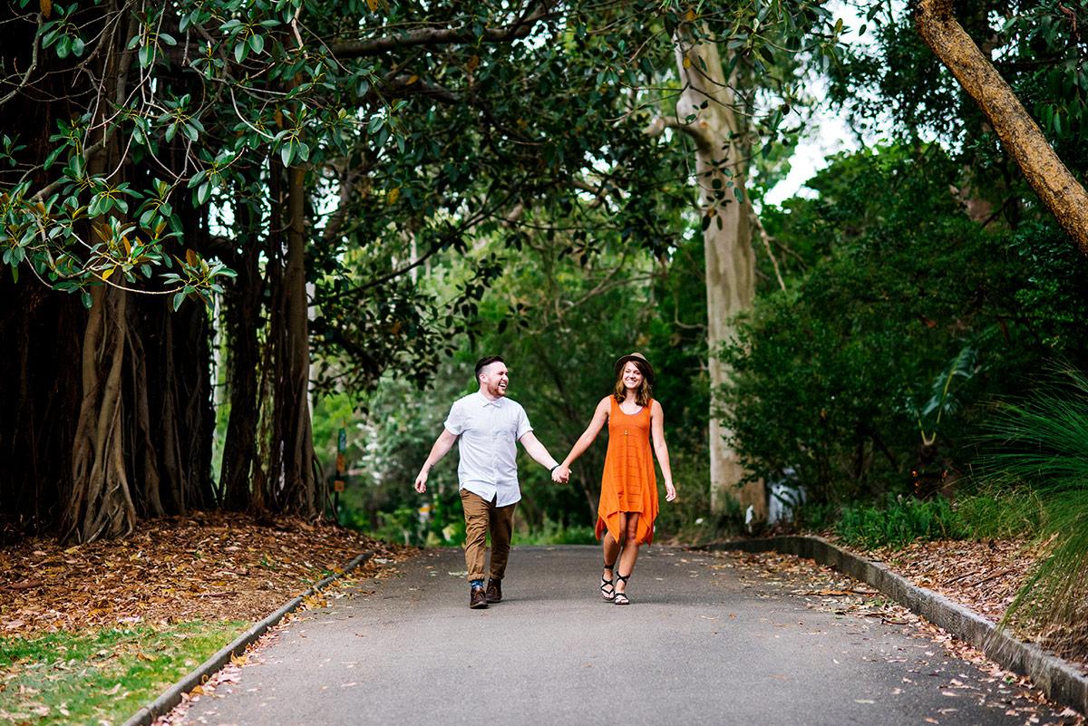 An engaged couple walks through the Botanic Gardens, Sydney