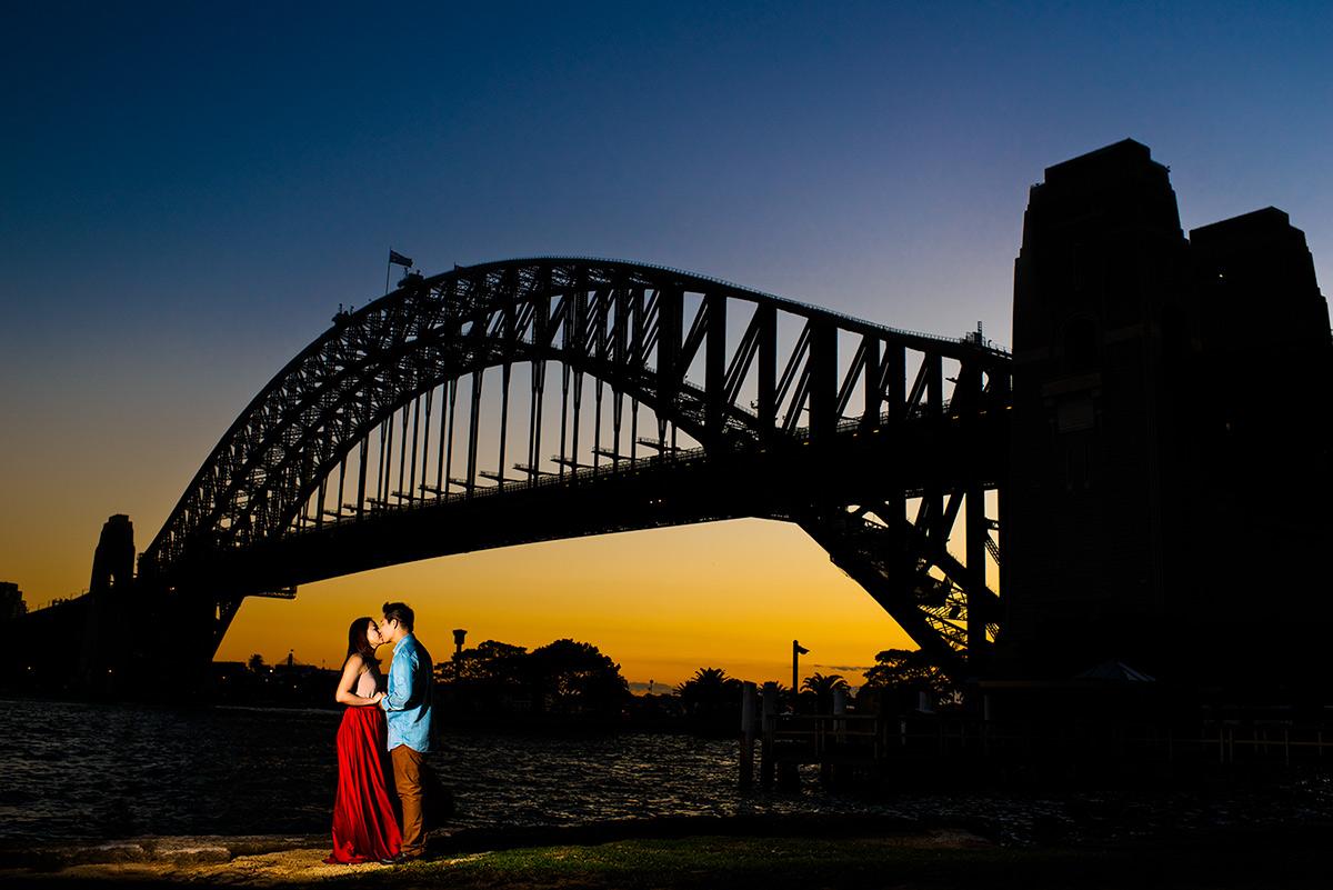 An engaged couple kisses under Sydney Opera House, Australia