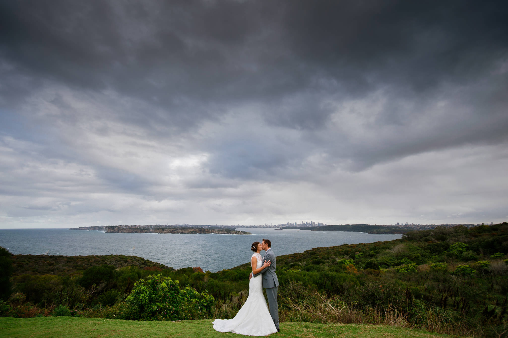 Newly married couple embrace at the lookout near North Head, Manly - a 2-minute drive from Milestone Events