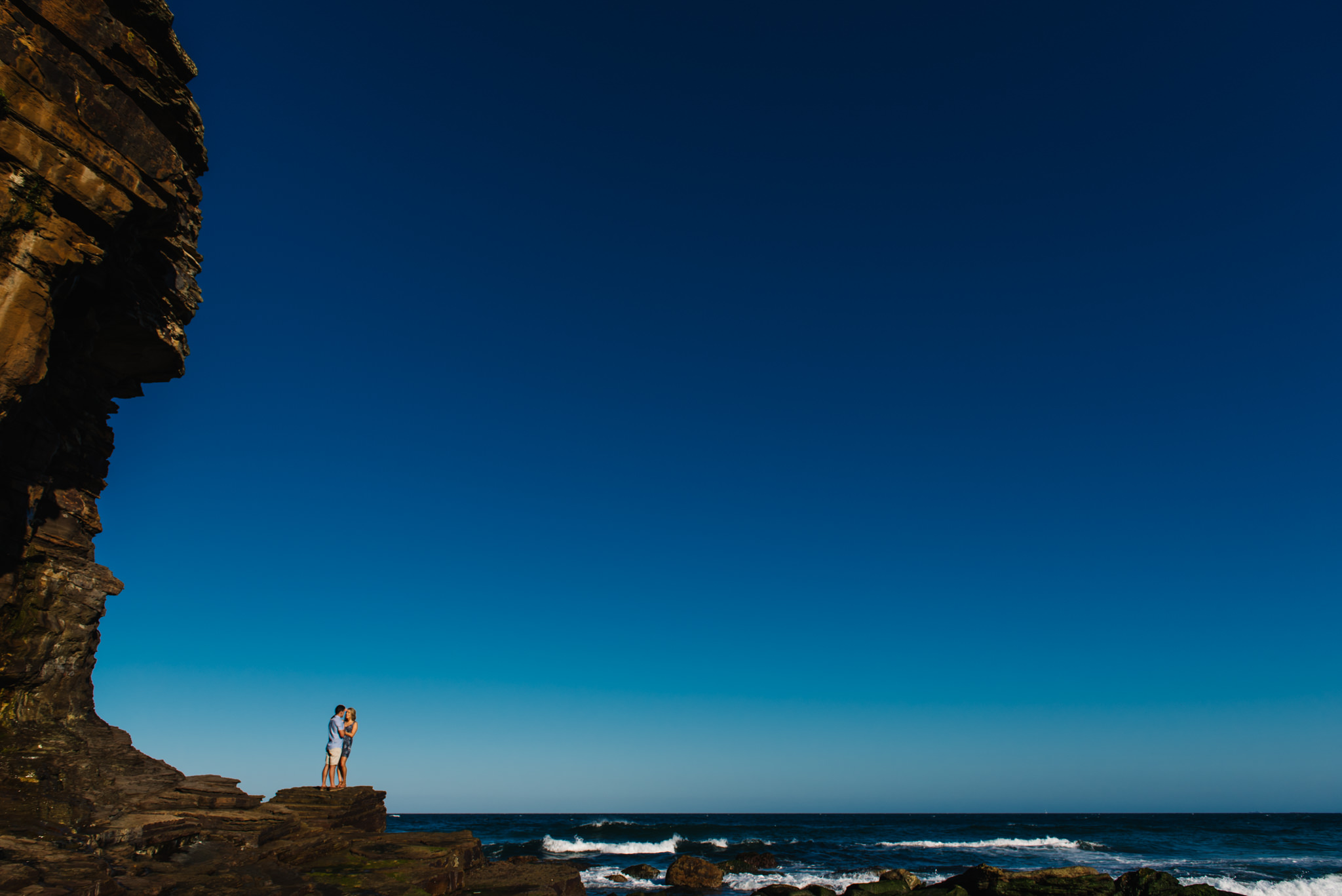 Engaged couple on rock outcropping at Turimetta beach