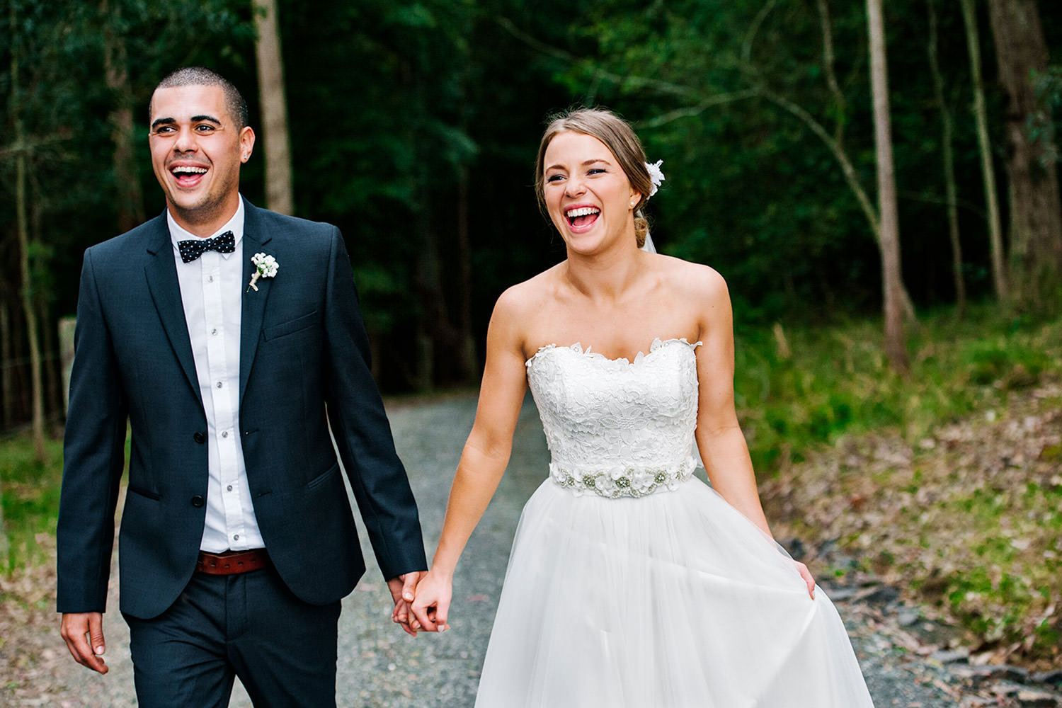 A newlywed couple walk along the entrance to Greenfield Farm Estate