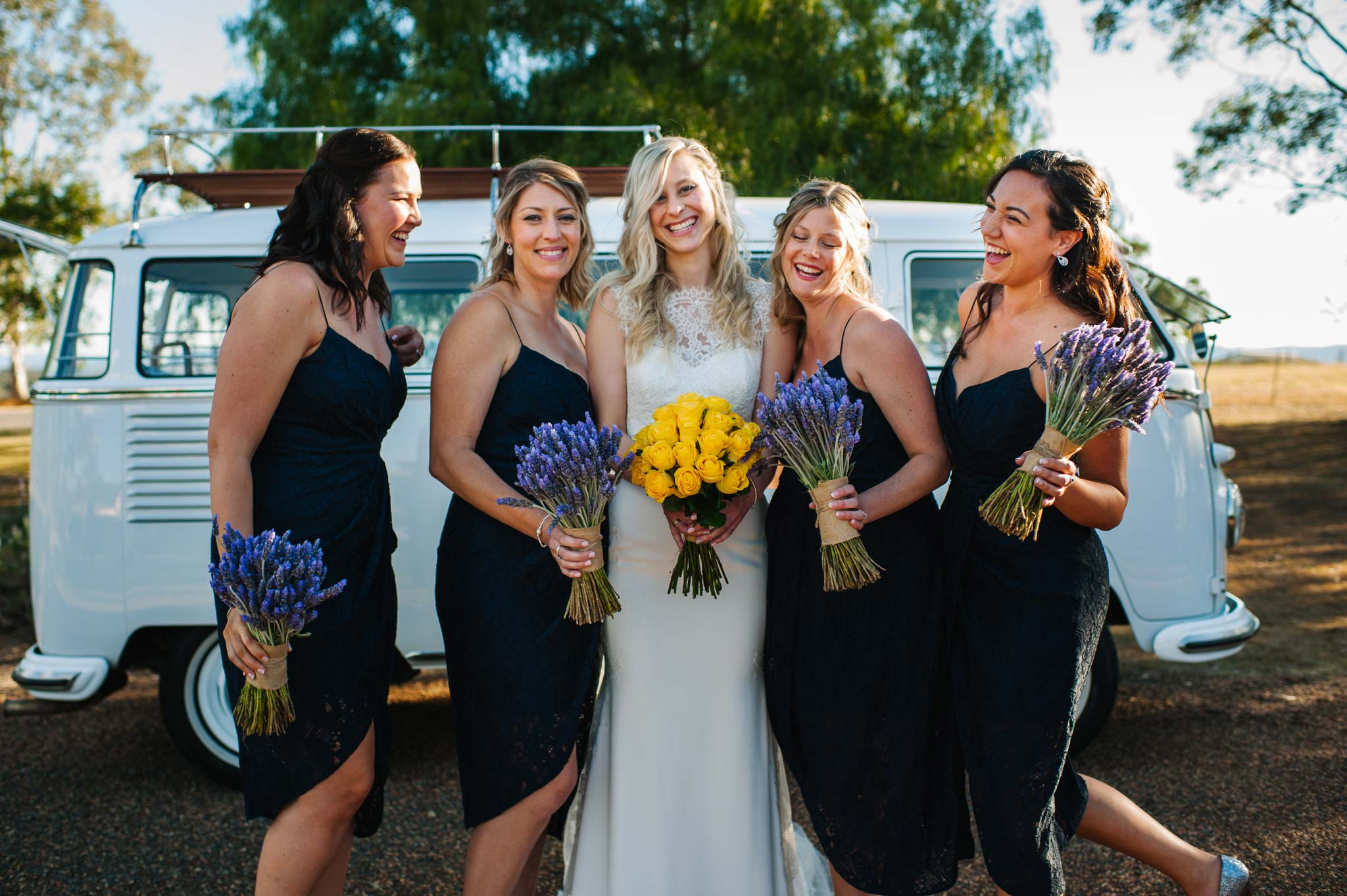 Bridesmaid and brides standing in front of a combi van