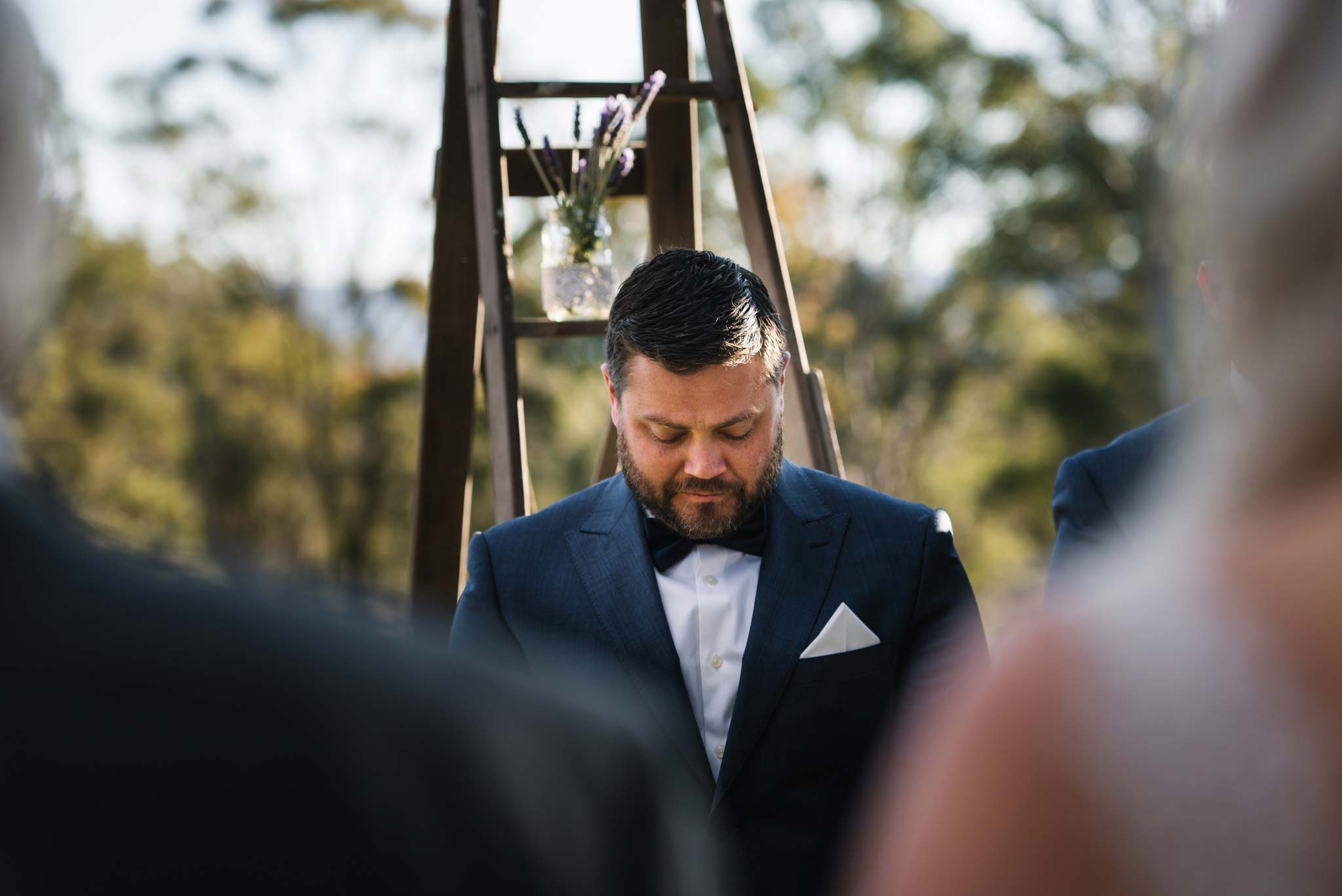 Emotional groom looks down as bride and father walk down aisle