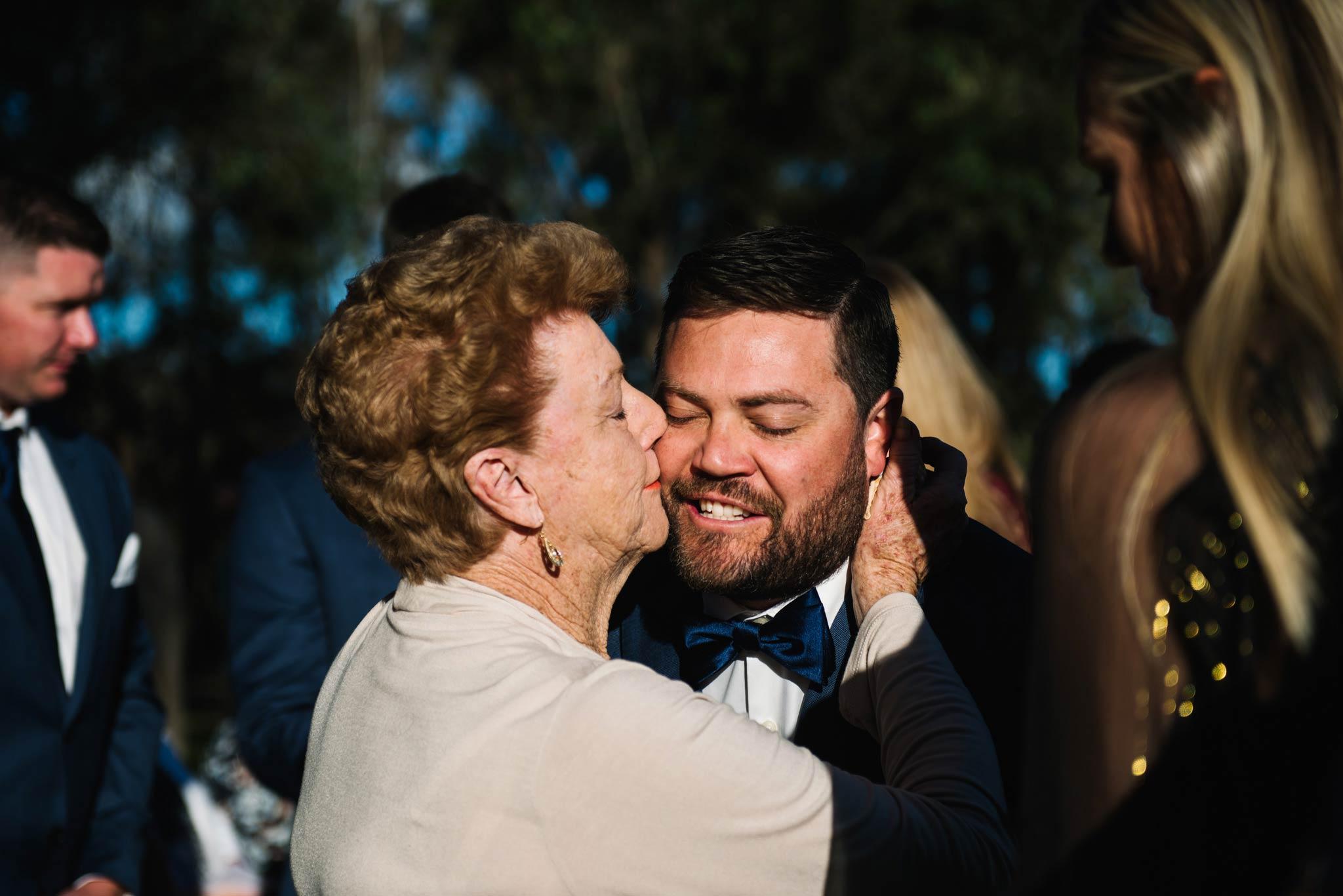 Grandma kisses groom on the cheek after wedding ceremony