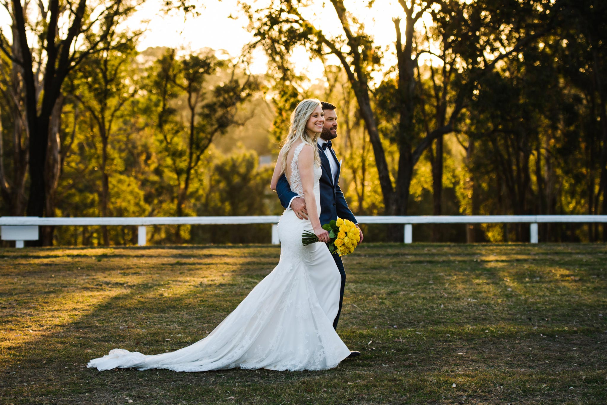 Bride and groom walking through field with colourful trees in background