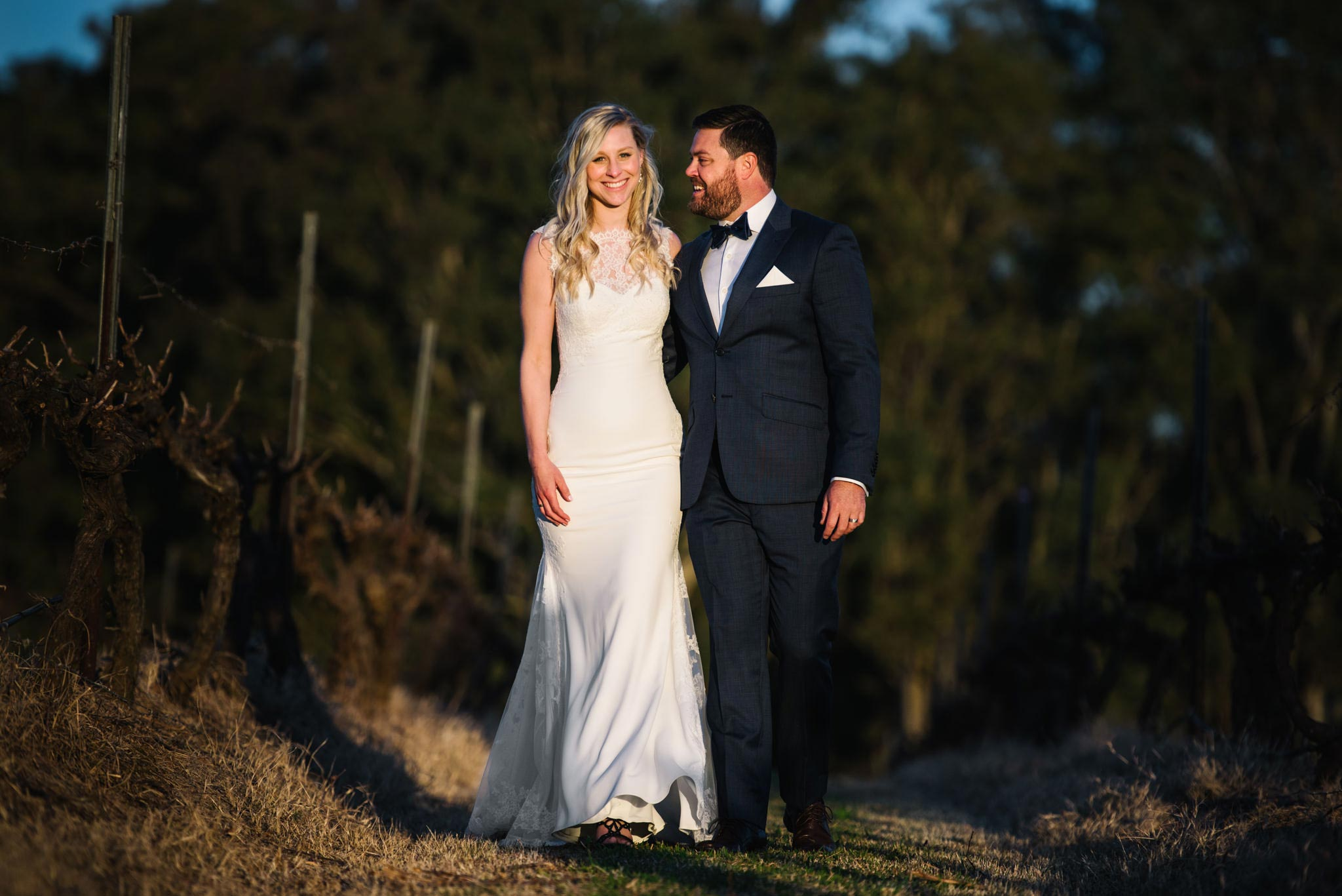 Newlyweds smiling and walking along country path