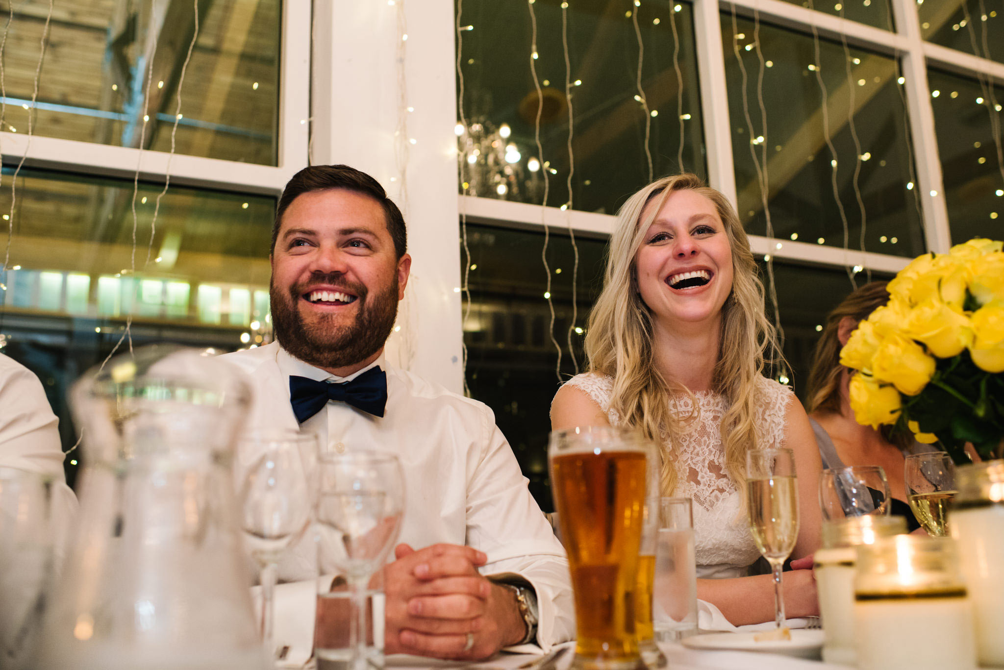 bride and groom laughing during father of the bride's speech