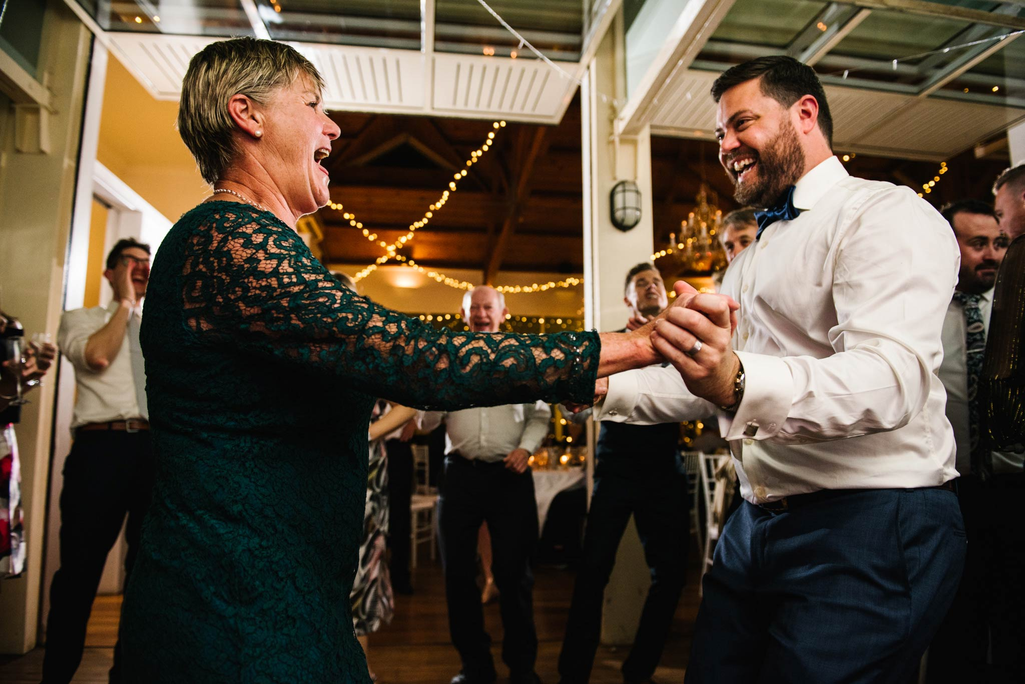 Mother and groom dancing together with guests watching in the background