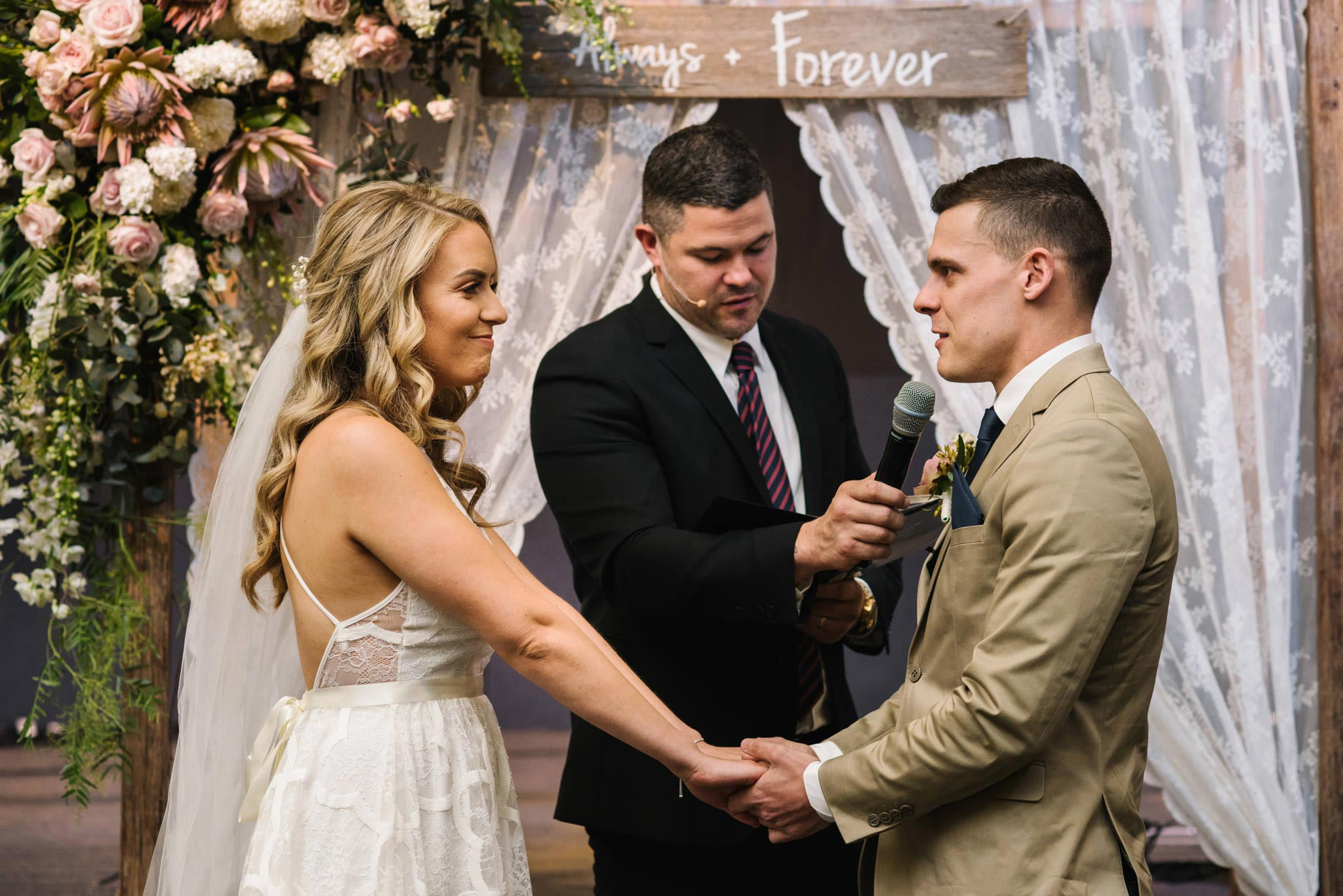 Bride and groom exchange vows in front of vintage lace altar