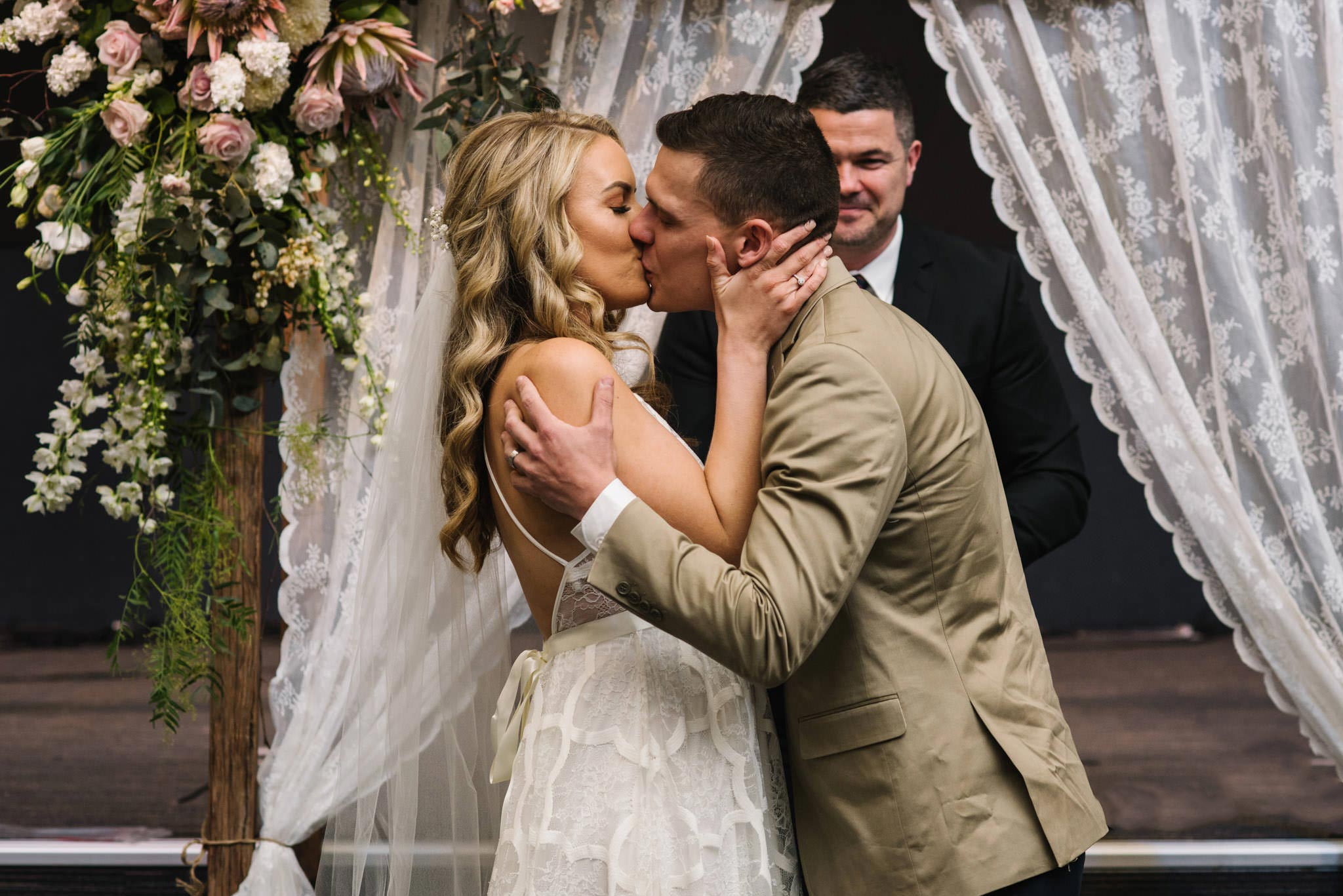 First kiss in front of lace altar