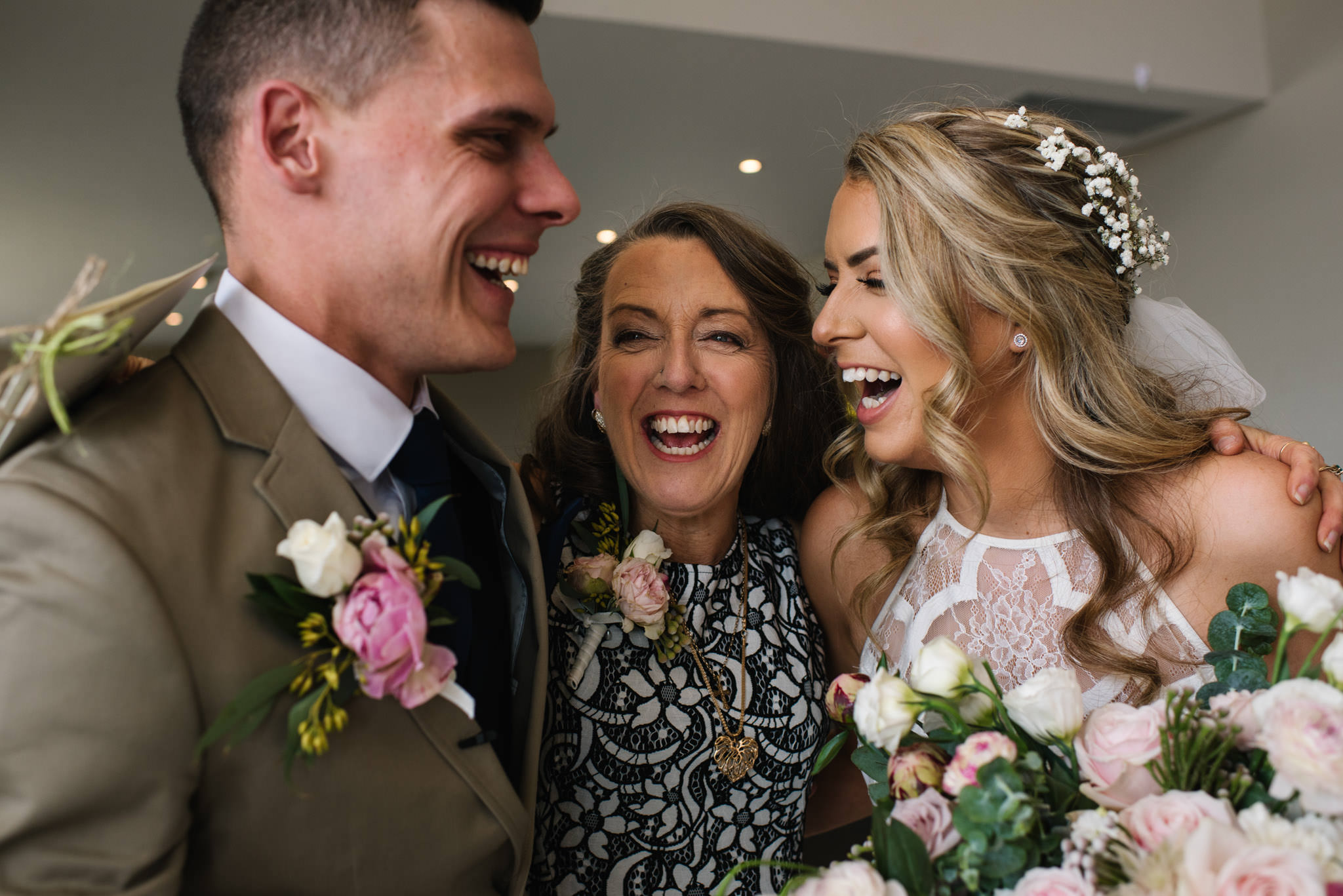 Mother of the bride embracing newlyweds