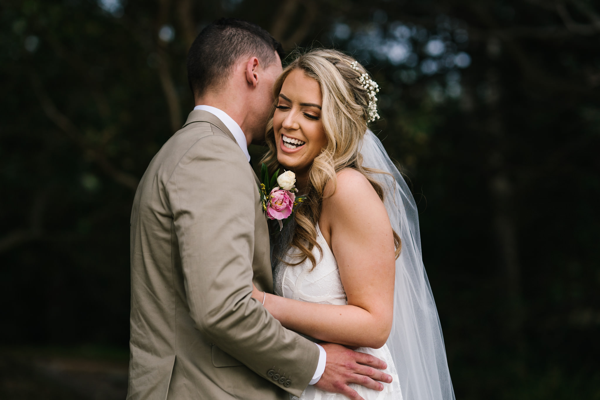 Bride smiling as groom embraces her