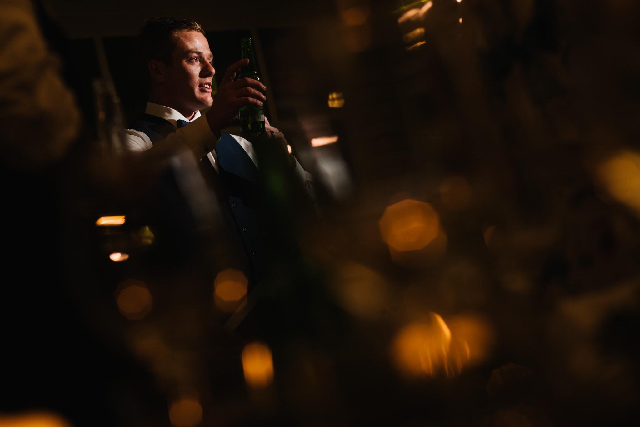 Best man giving speech amongst candlelight