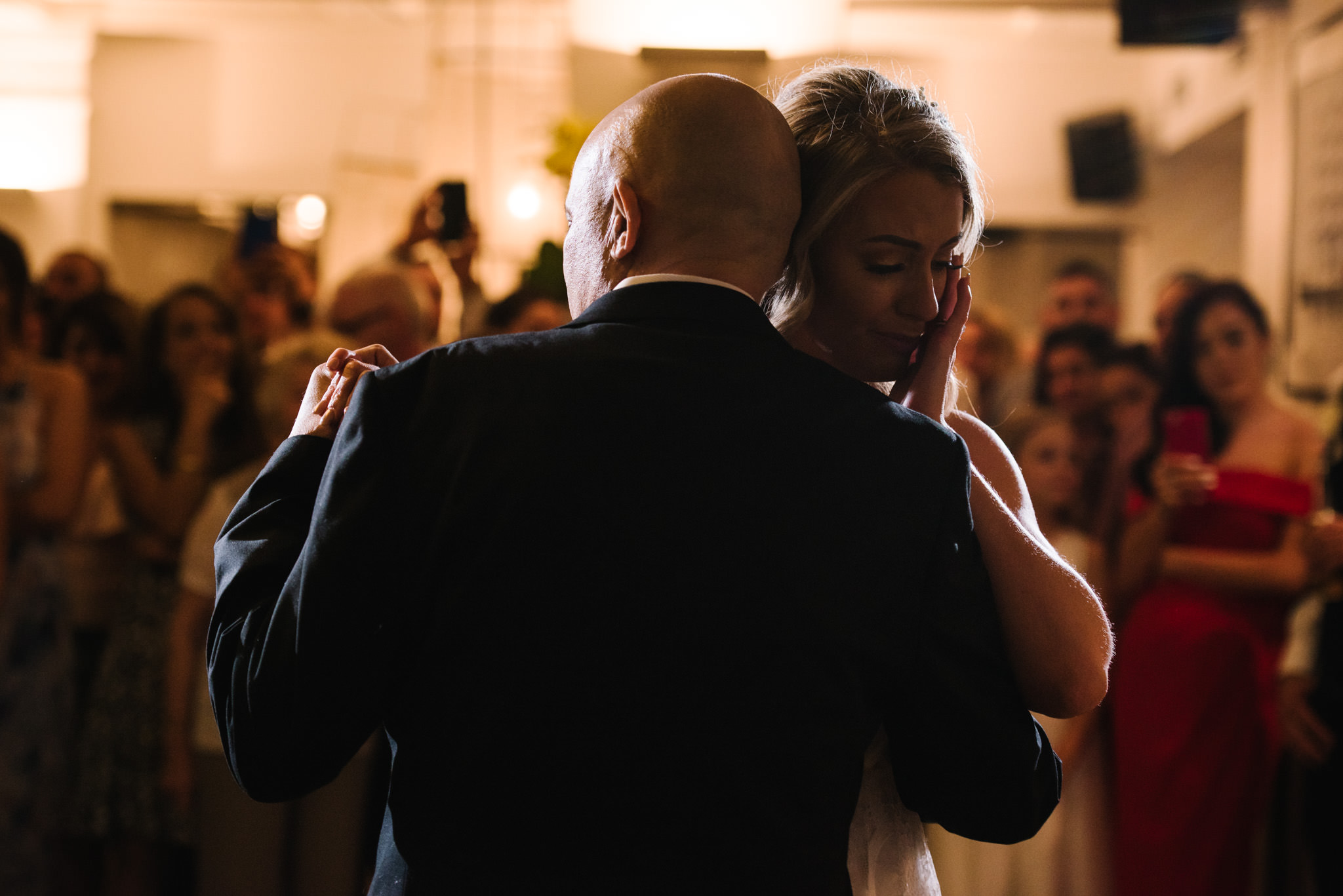 Bride crying as she dances with her dad