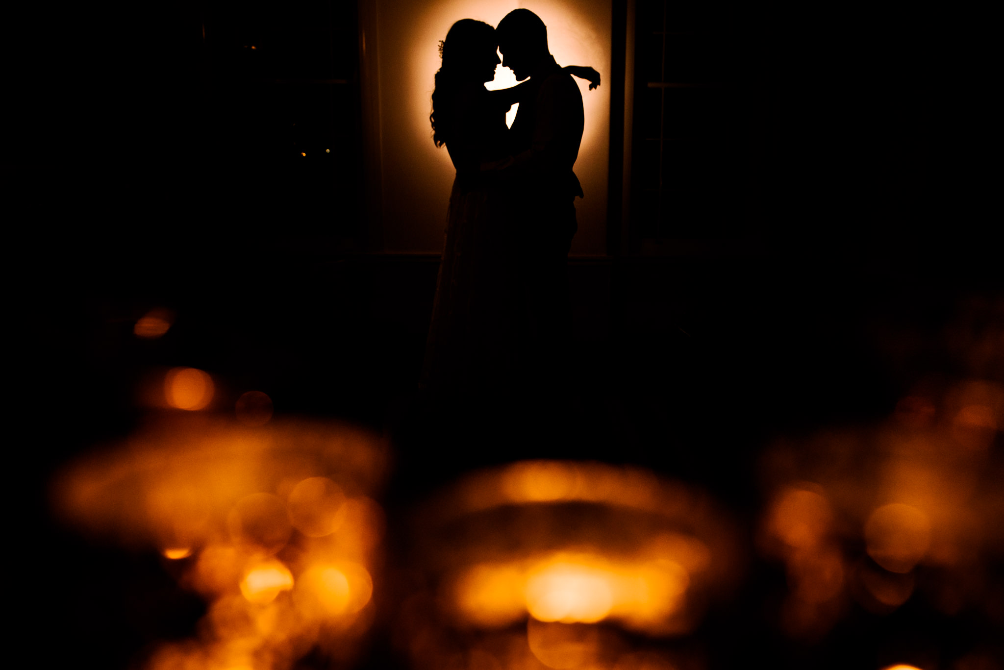 Bride and groom embrace amongst candlelight at wedding reception