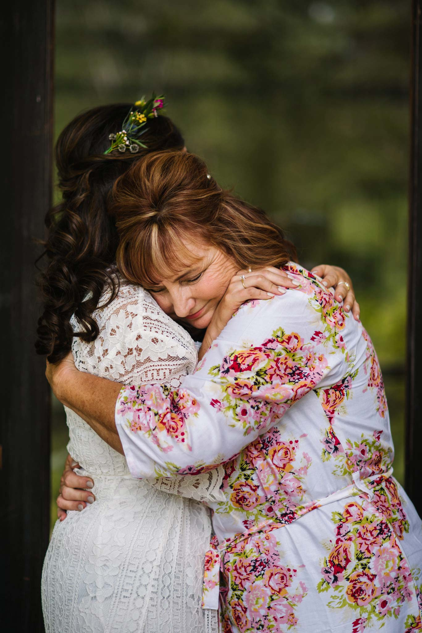 Mother of the bride hugs her daughter tightly
